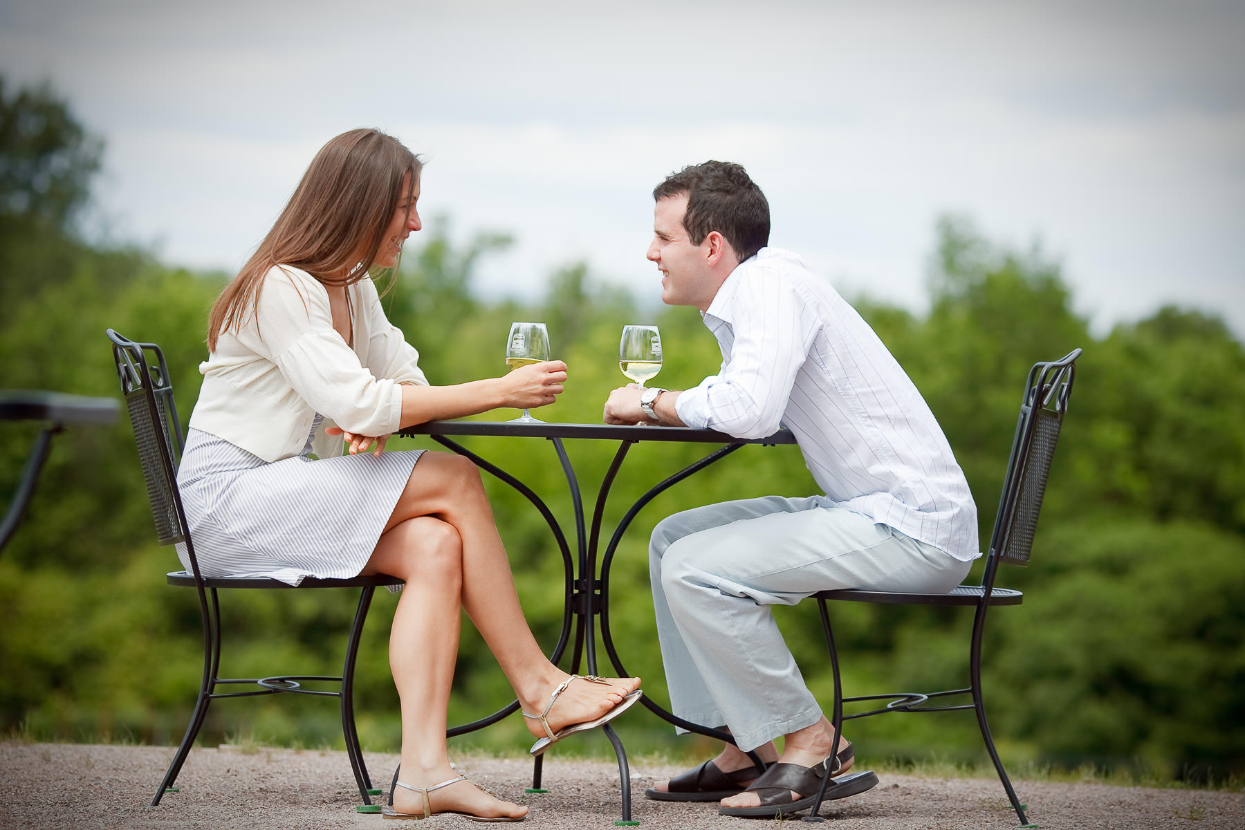 A couple drinks wine together on the patio at the Shelburne Vineyard during their Vermont engagement session