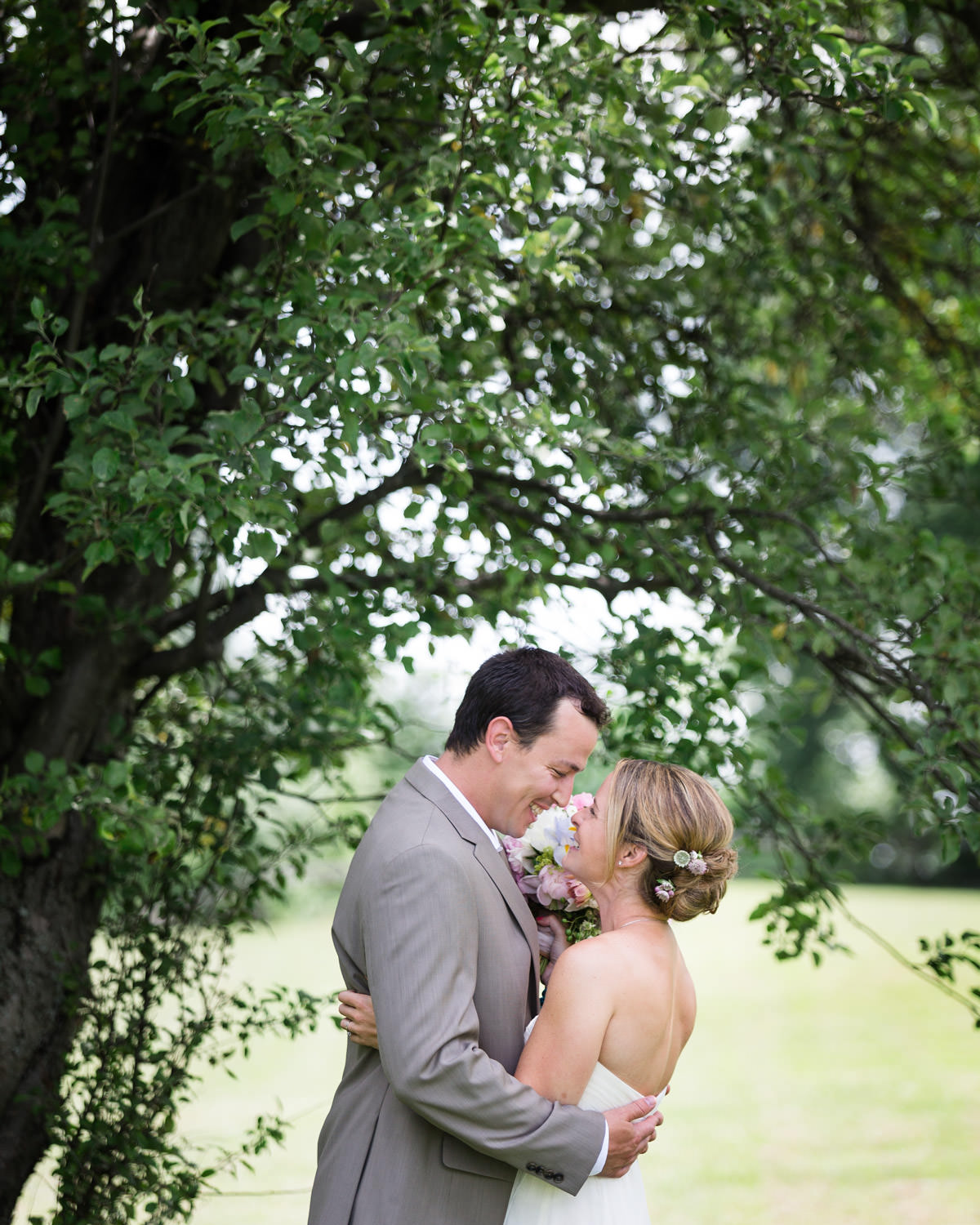 A couple embraces under and apple tree at the Grand Isle Lake House during a first look by wedding photographer Stina Booth