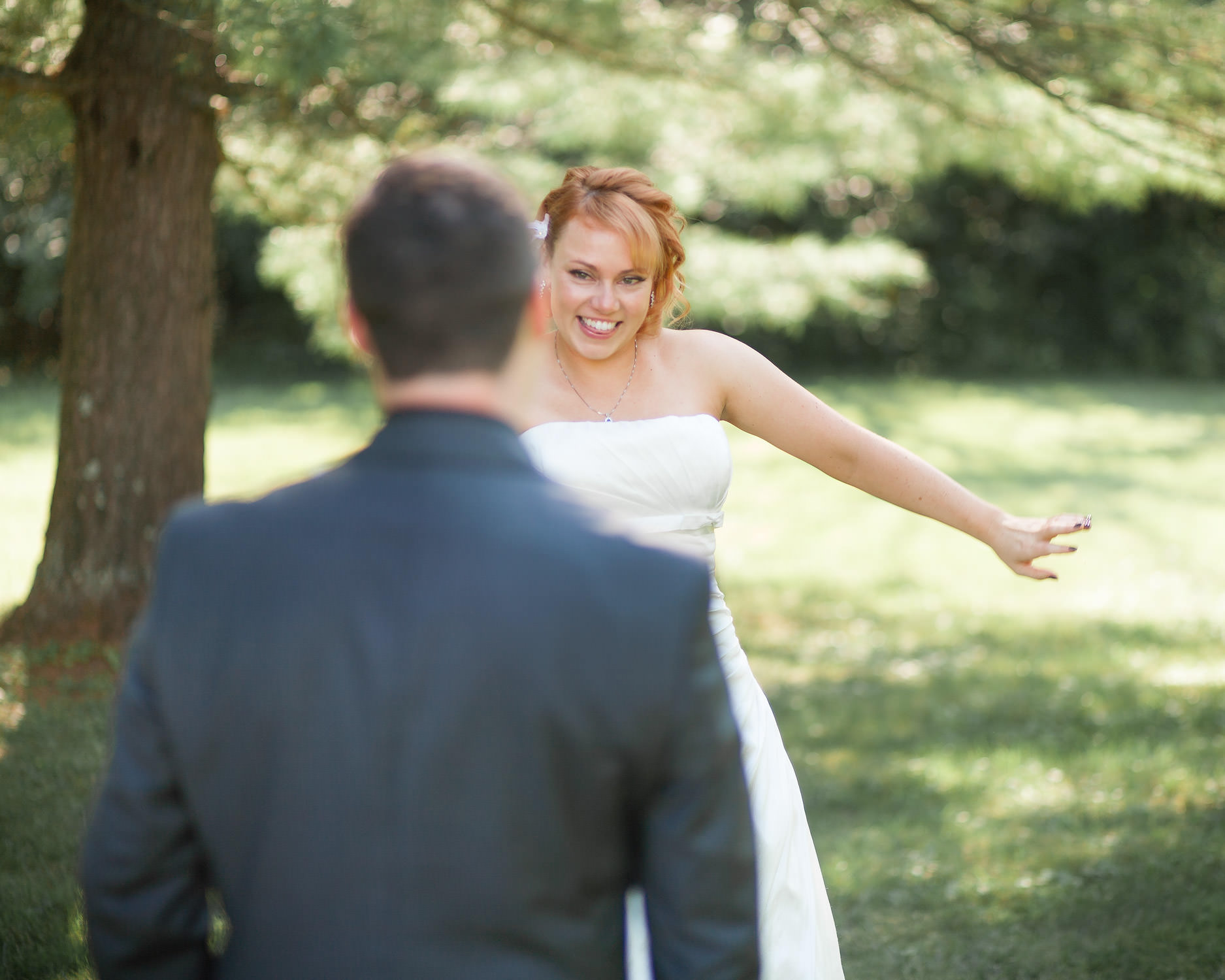 A bride shows off her wedding dress during a pre-ceremony first look by Vermont wedding photographer Stina Booth