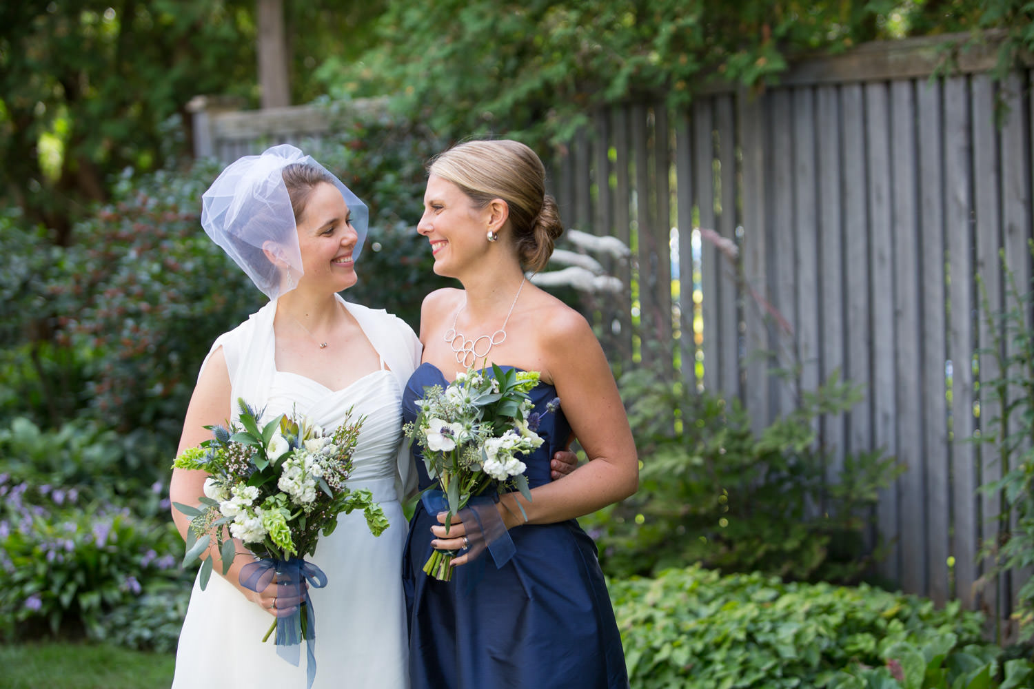 A family wedding group portrait of a bride and her sister in Montpelier Vermont by wedding photographer Stina Booth