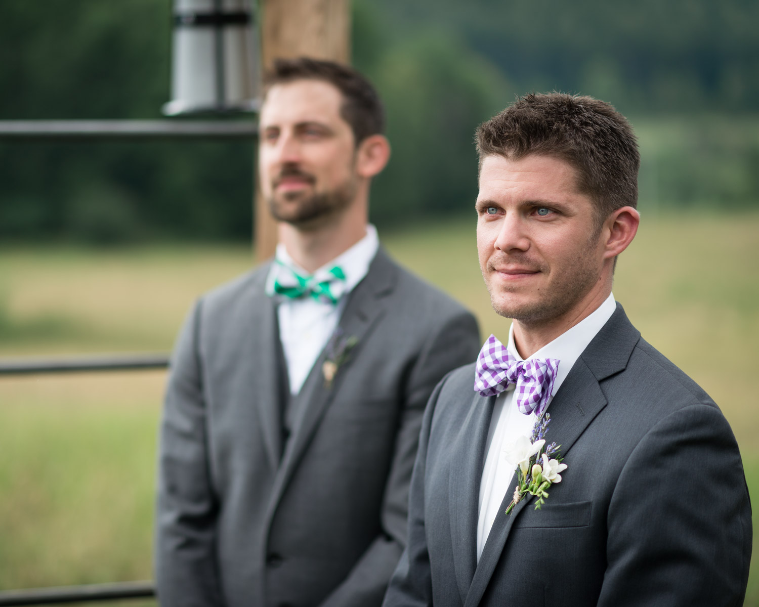A groom watches his bride walk down the aisle in the ceremony field at Bliss Ridge by wedding photographer Stina Booth