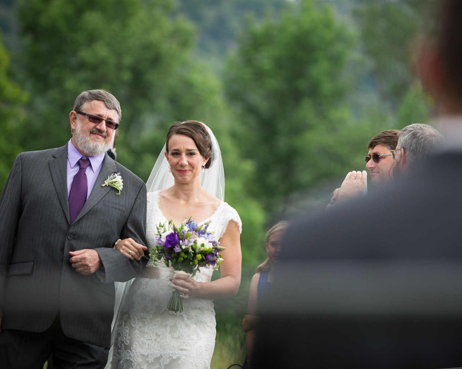 A bride looks toward her groom as she walks down the aisle with her father in the ceremony field at Bliss Ridge by wedding photographer Stina Booth