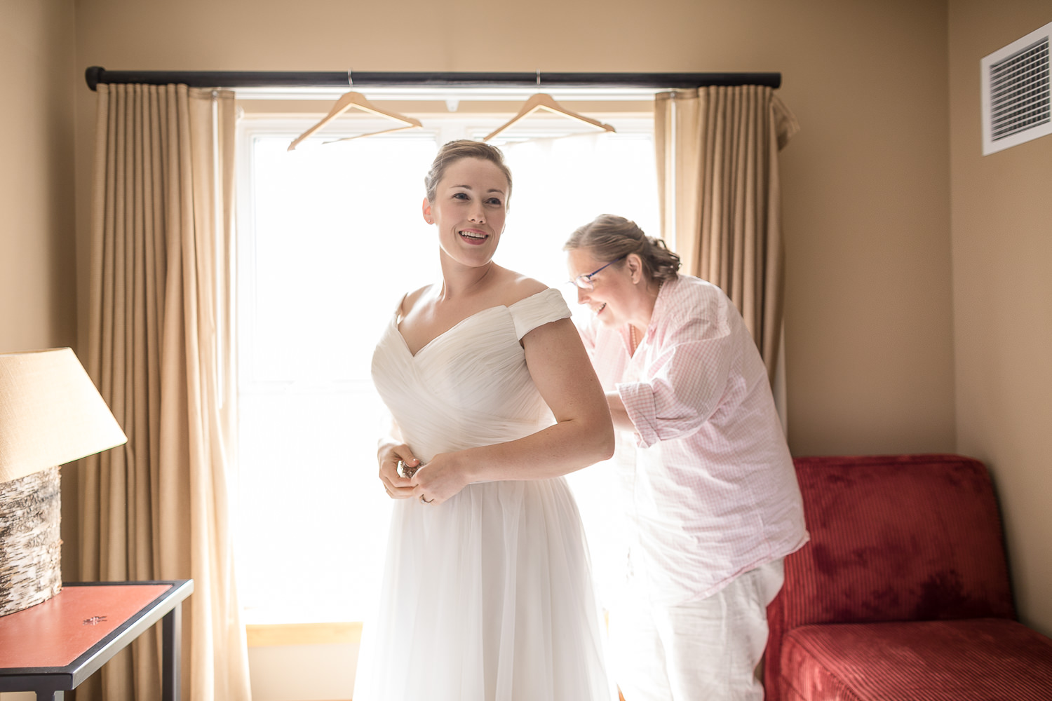 a bride's Mom helps her with her wedding gown