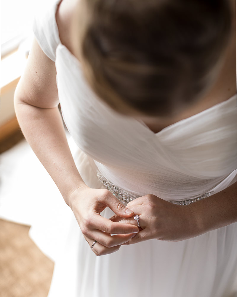 the bride adjusts her engagement ring before a summer wedding at Jay Peak Resort by Stina Booth of Studio SB wedding photography Vermont, vermont wedding photographers