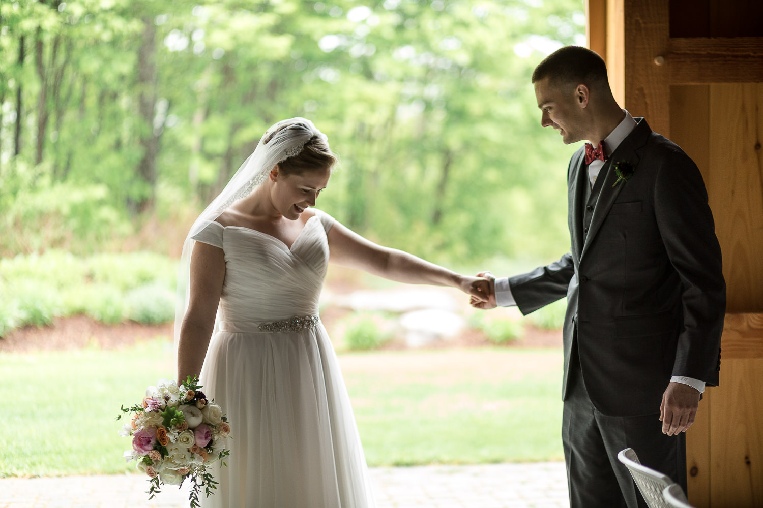 a bride and groom take each other in during their first look before their Jay Peak Resort summer wedding in a photo by Stina Booth