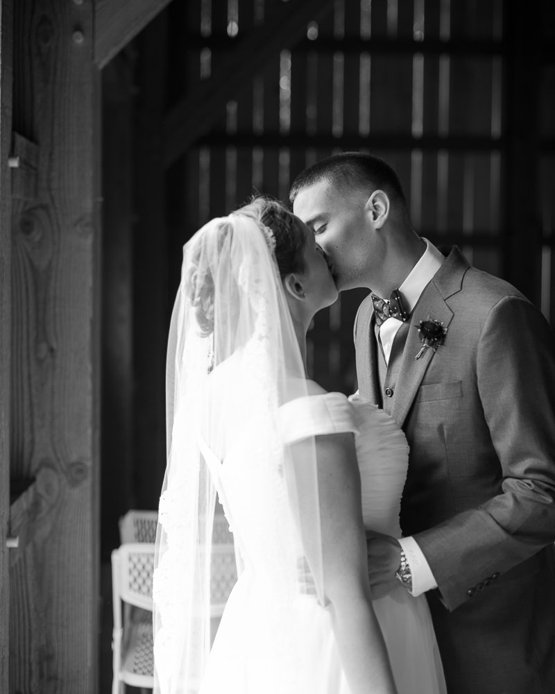 a couple kisses during their first look at Jay Peak Resort in a photo by Vermont wedding photographer Stina Booth