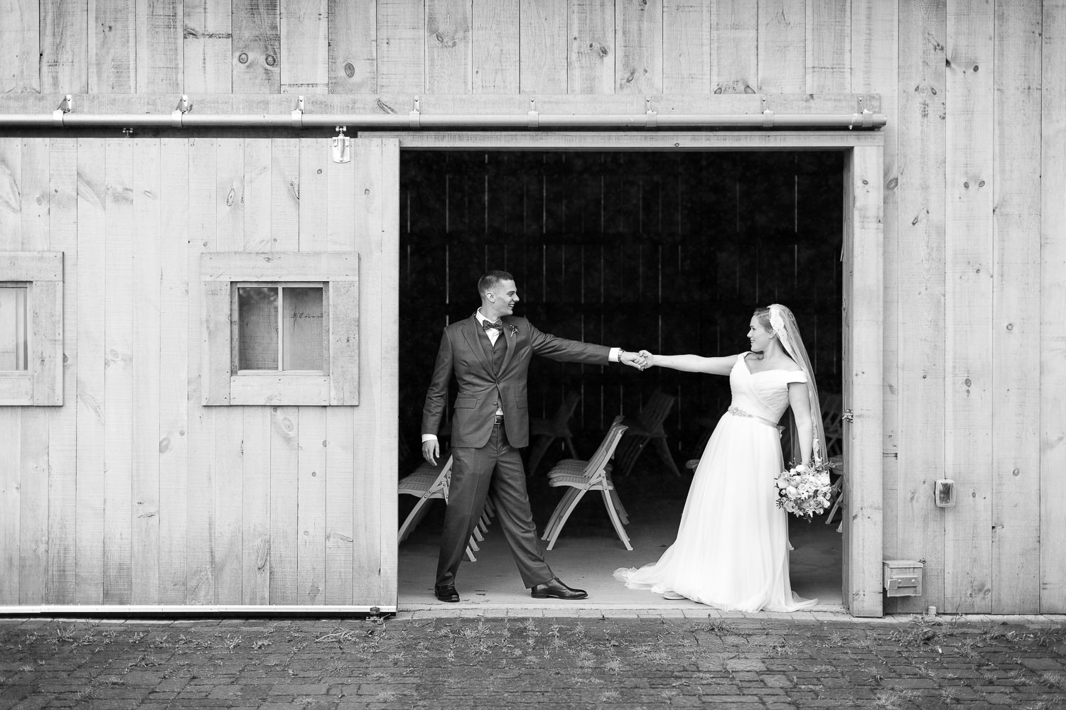 a wedding couple holding hands in the Jay Peak Resort wedding barn by Stina Booth