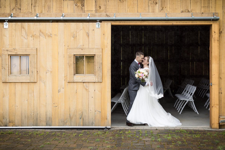 a bride and groom embrace in a doorway of the Jay Peak Resort wedding barn