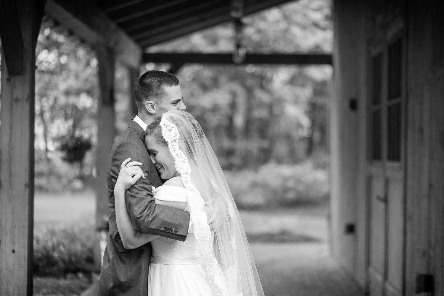 a couple hugs during their first look before their wedding at the Jay Peak Resort wedding barn in a photo by photographer Stina Booth