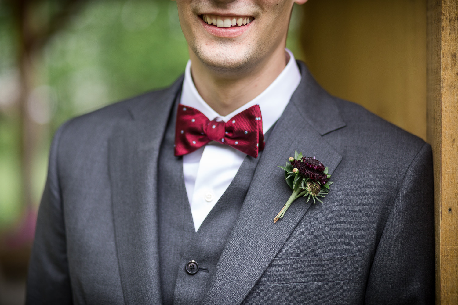 a plum colored boutonniere by floral artistry