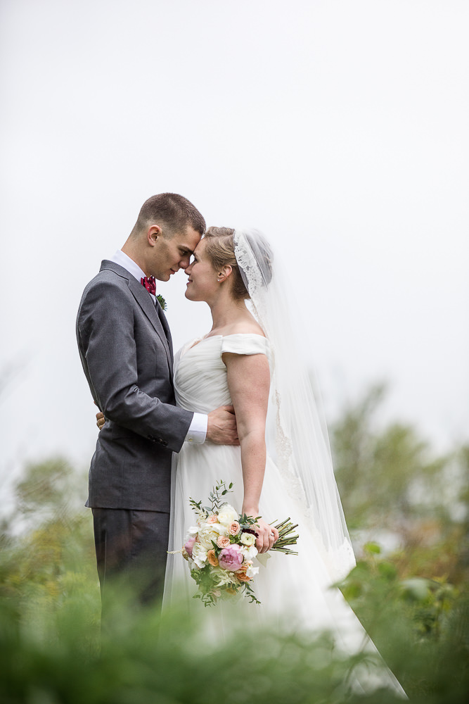 a portrait of a bride and groom on a misty wedding day at the Jay Peak Resort by photographer Stina Booth