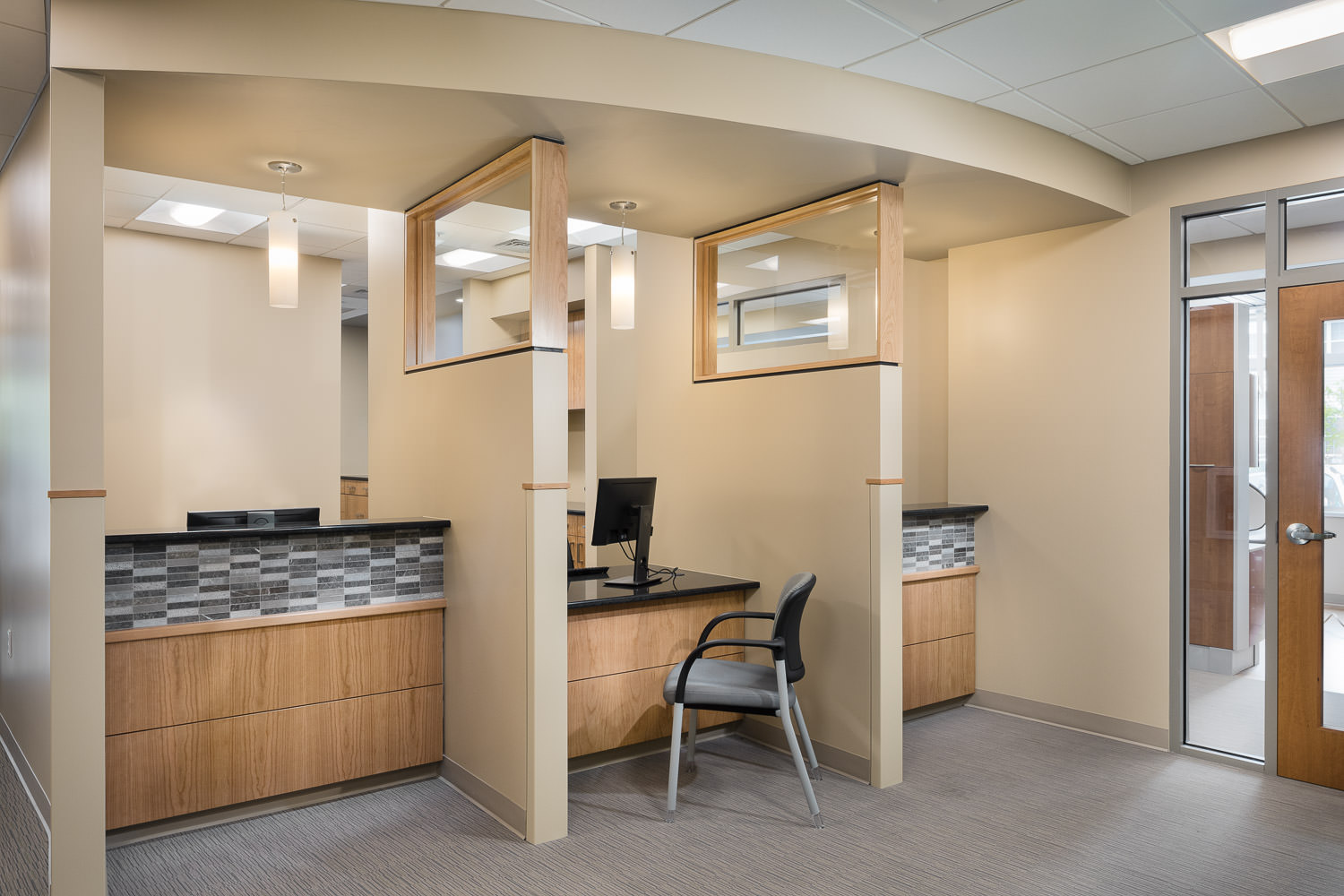 Photo of the patient check-in desks in the new Timberlane Dental Office in Essex Vermont with interior design by BSD Interior Design and construction by Neagley & Chase photographed by Studio SB.