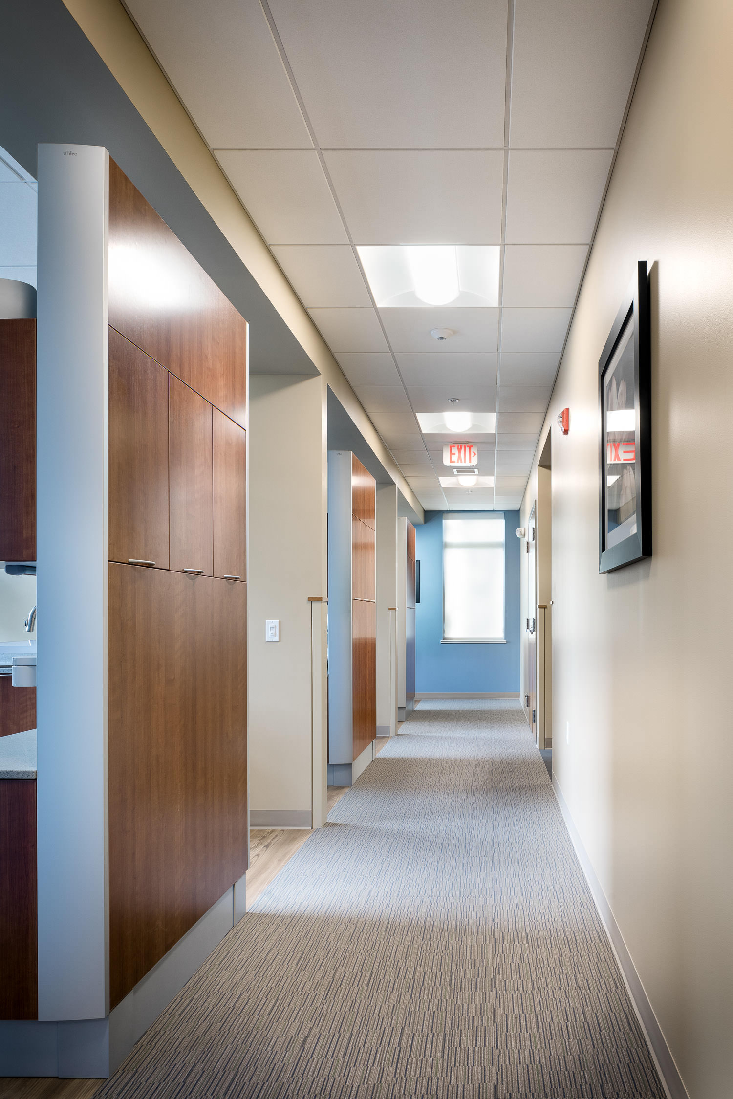 Photo of a hallway with custom cabinetry in the new Timberlane Dental Office in Essex Vermont with interior design by BSD Interior Design and construction by Neagley & Chase photographed by Studio SB.