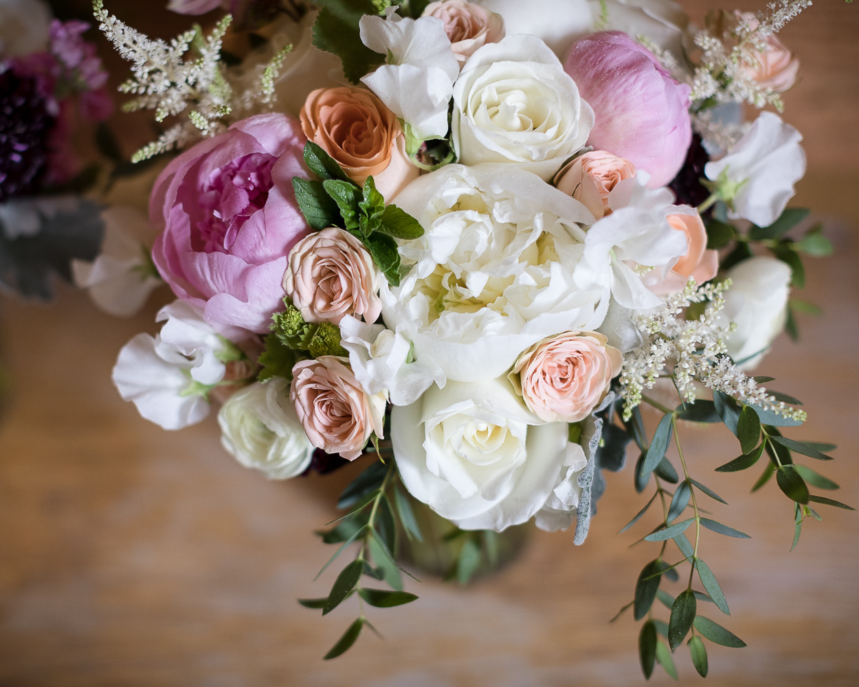 A pink and white wedding bouquet with peonies and roses
