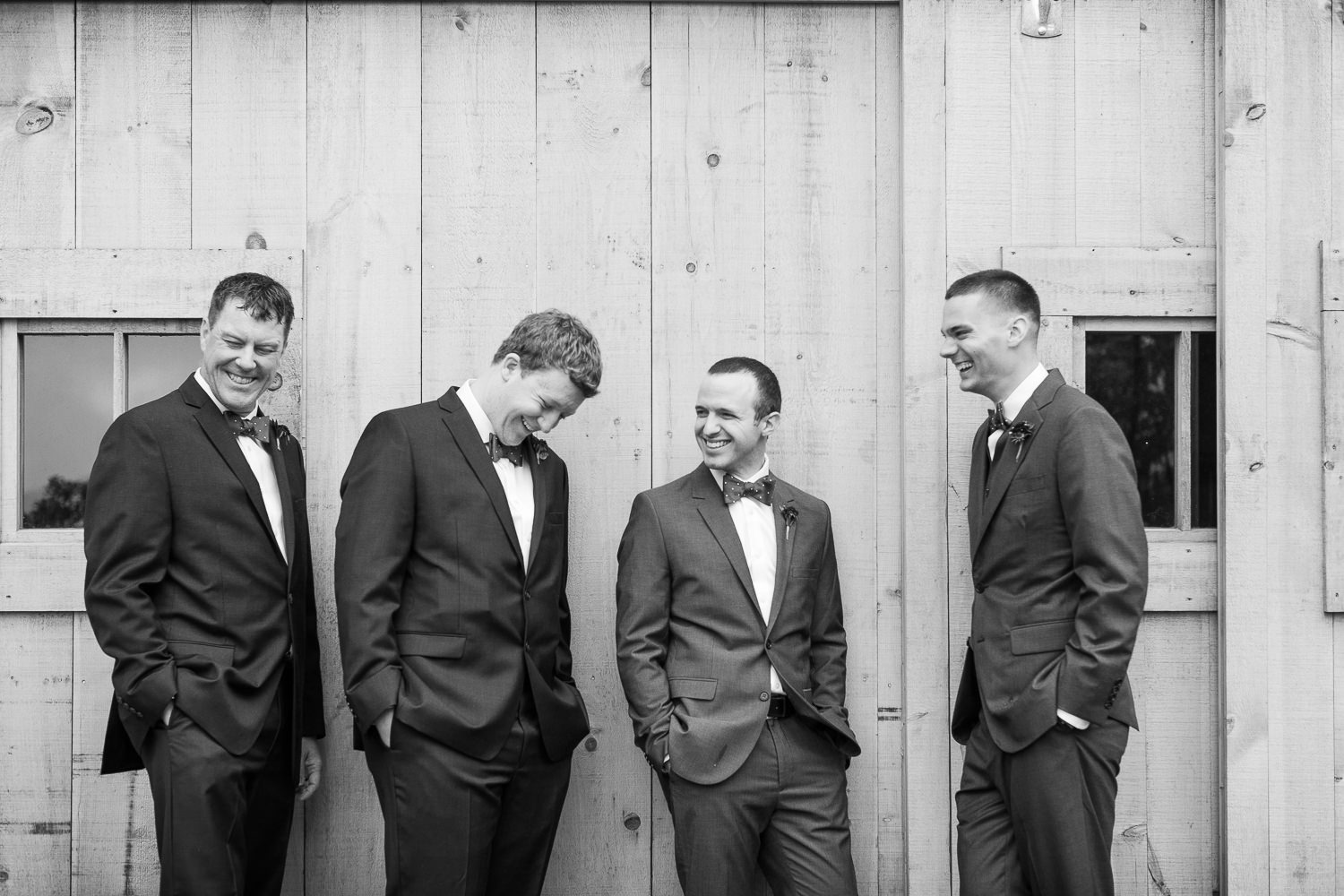 a photo of the groomsmen laughing in front of the barn at the Jay Peak Resort in a photo by Stina Booth