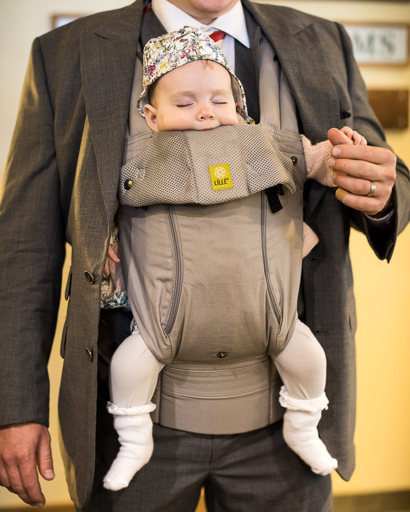 a baby napping in a baby bjorn before a wedding at Jay Peak Resort by photographer Stina Booth