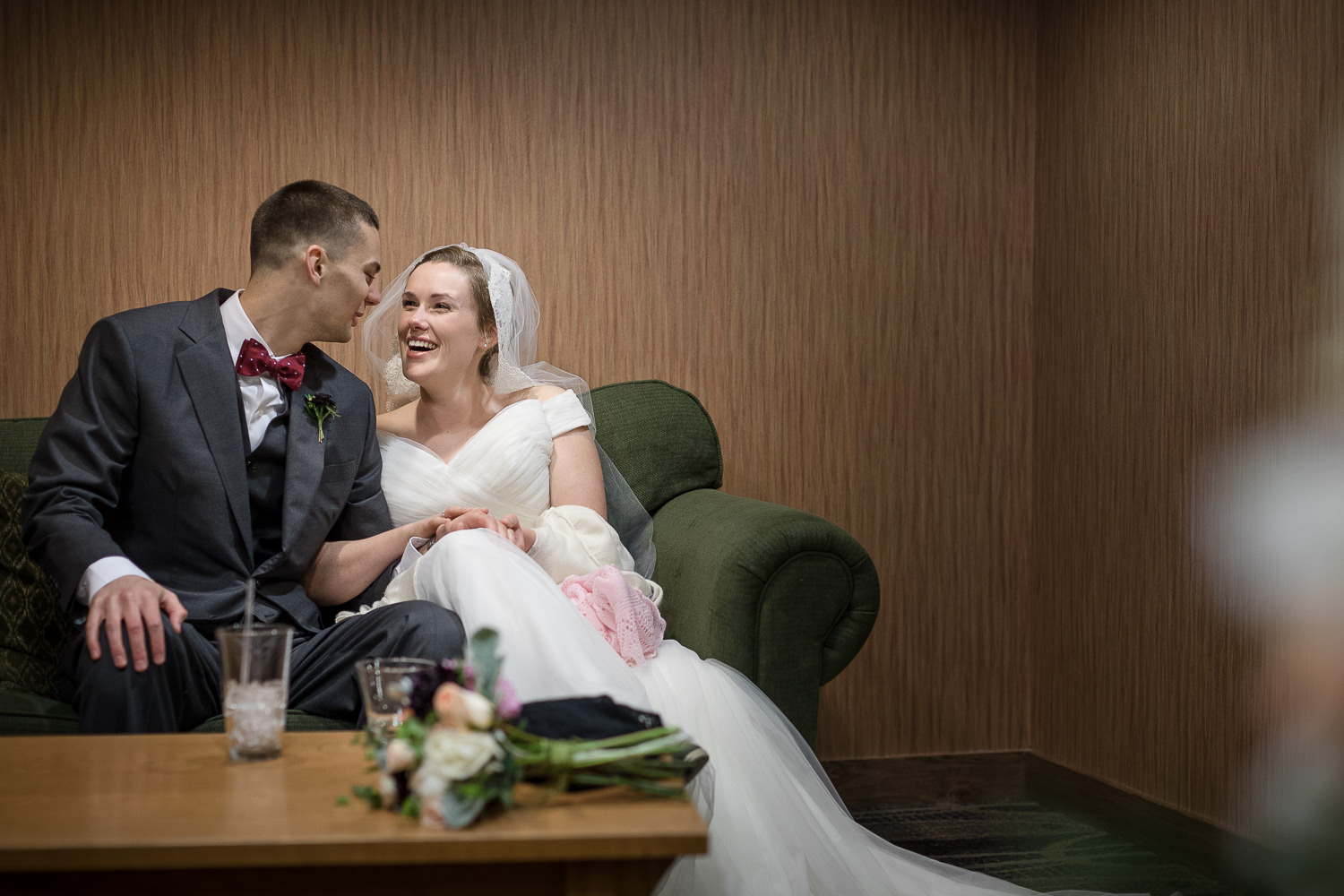 a couple shares a quiet moment sitting on a couch while waiting before their Jay Peak Resort wedding