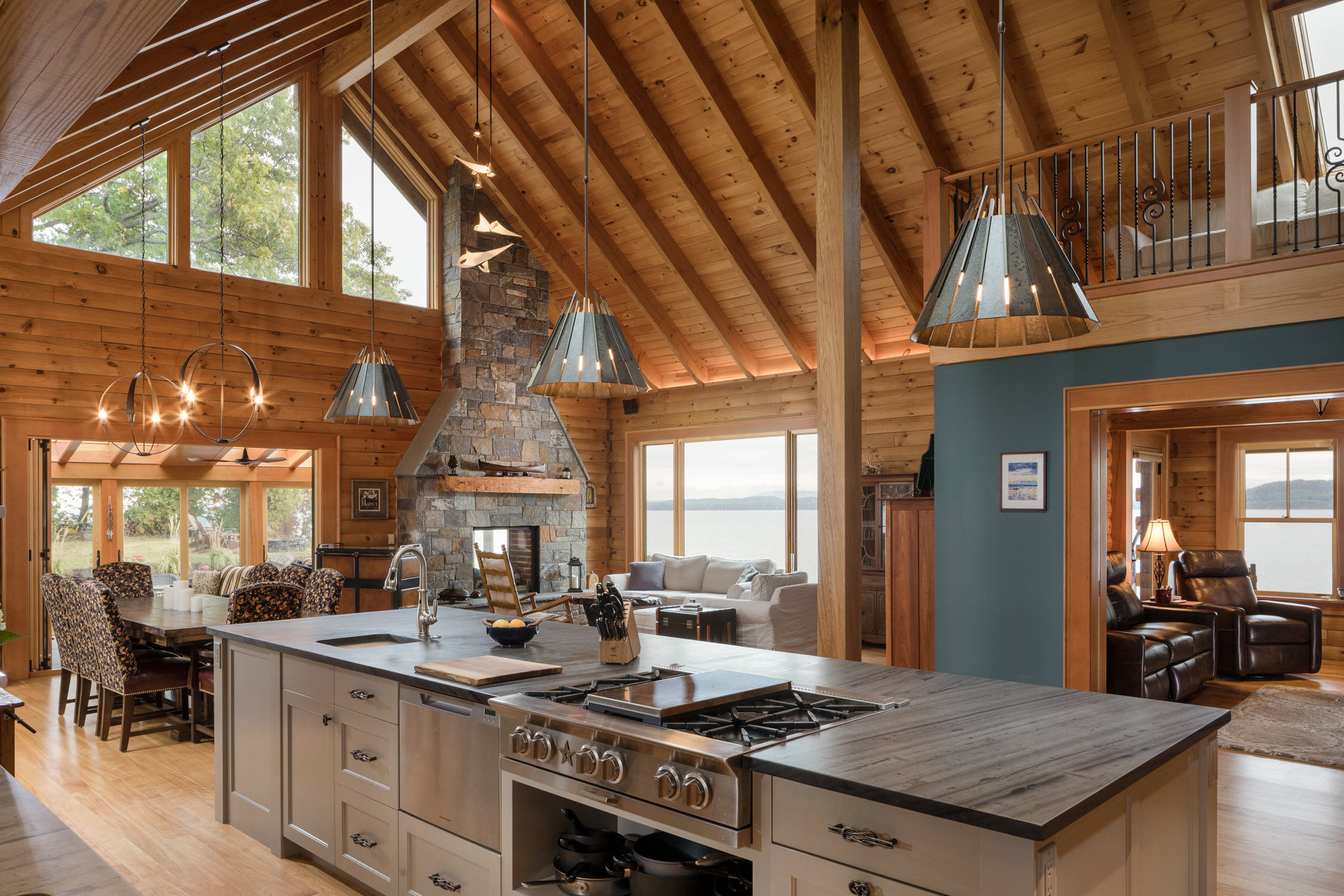Interior architecture photo of an Adirondack style lake house renovation including an open kitchen and living concept, timber framing and wood paneling throughout designed by Wiemann Lamphere Architects and photographed by Vermont photographer Stina Booth of Studio SB.,