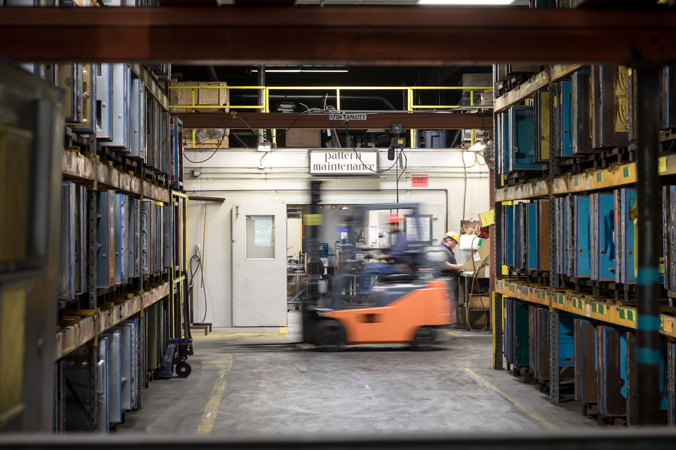 Photo of a forklift driving past racks of molds at the Vermont Casting foundry in Randolph Vermont taken by commercial photographer Stina Booth