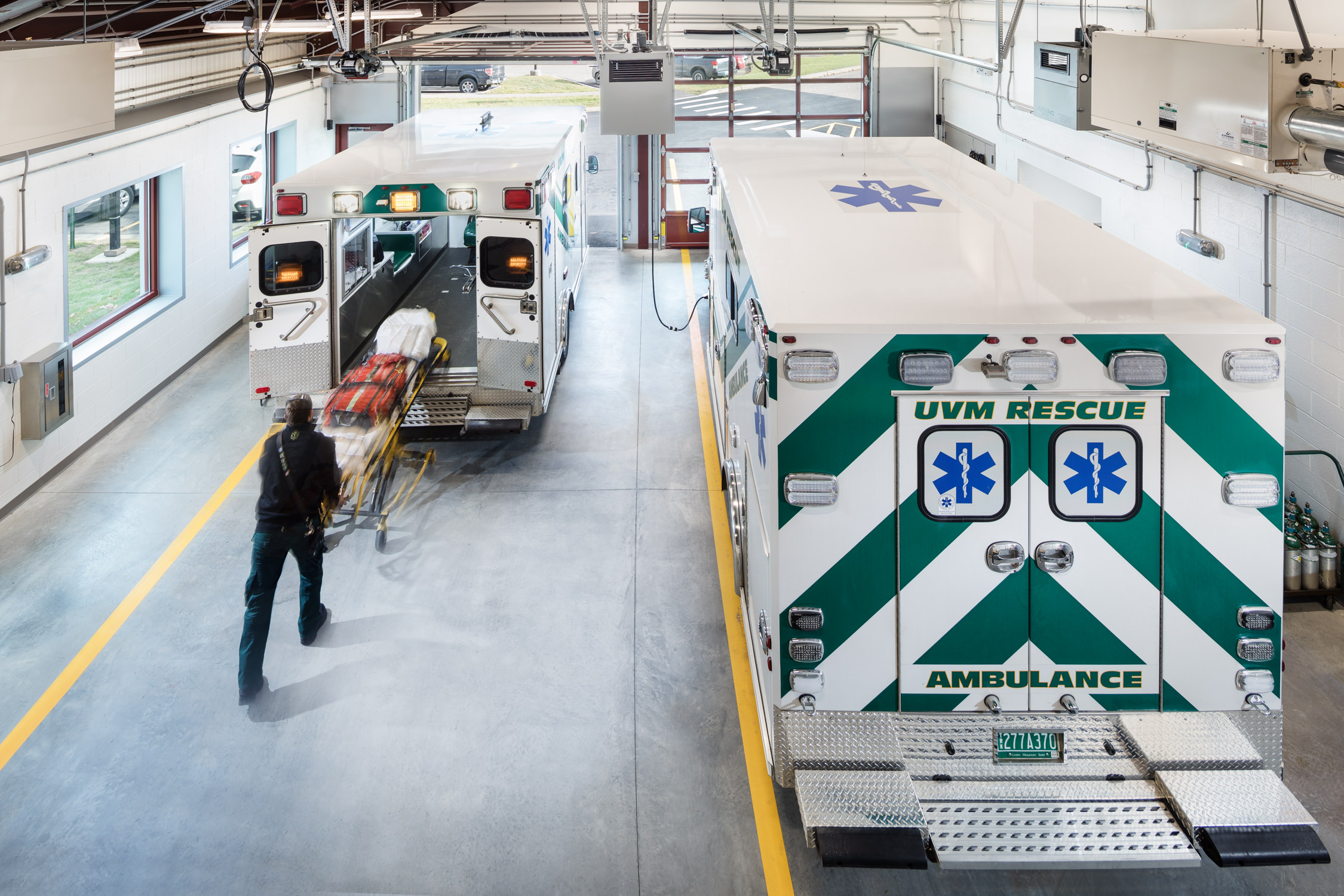 A view of an ambulance being loaded in the truck bays in the UVM Rescue building in Burlington VT by Vermont professional photographer Stina Booth