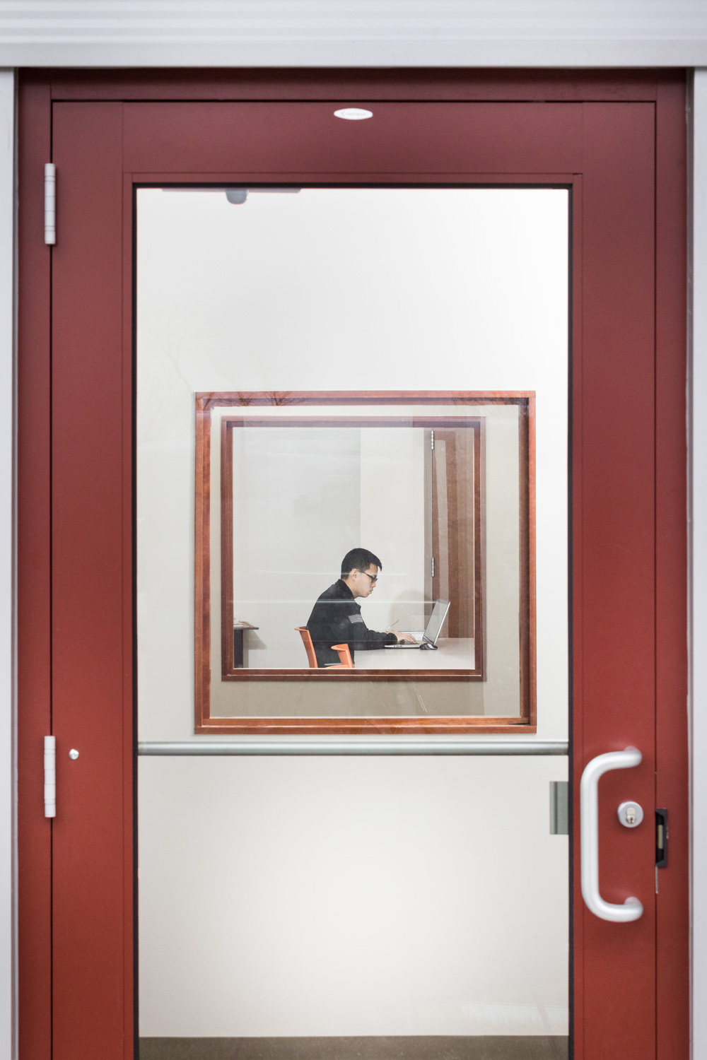 A view through an exterior glass door and aligned interior windows into the provider conference room in the UVM Rescue building in Burlington VT by Vermont professional photographer Stina Booth