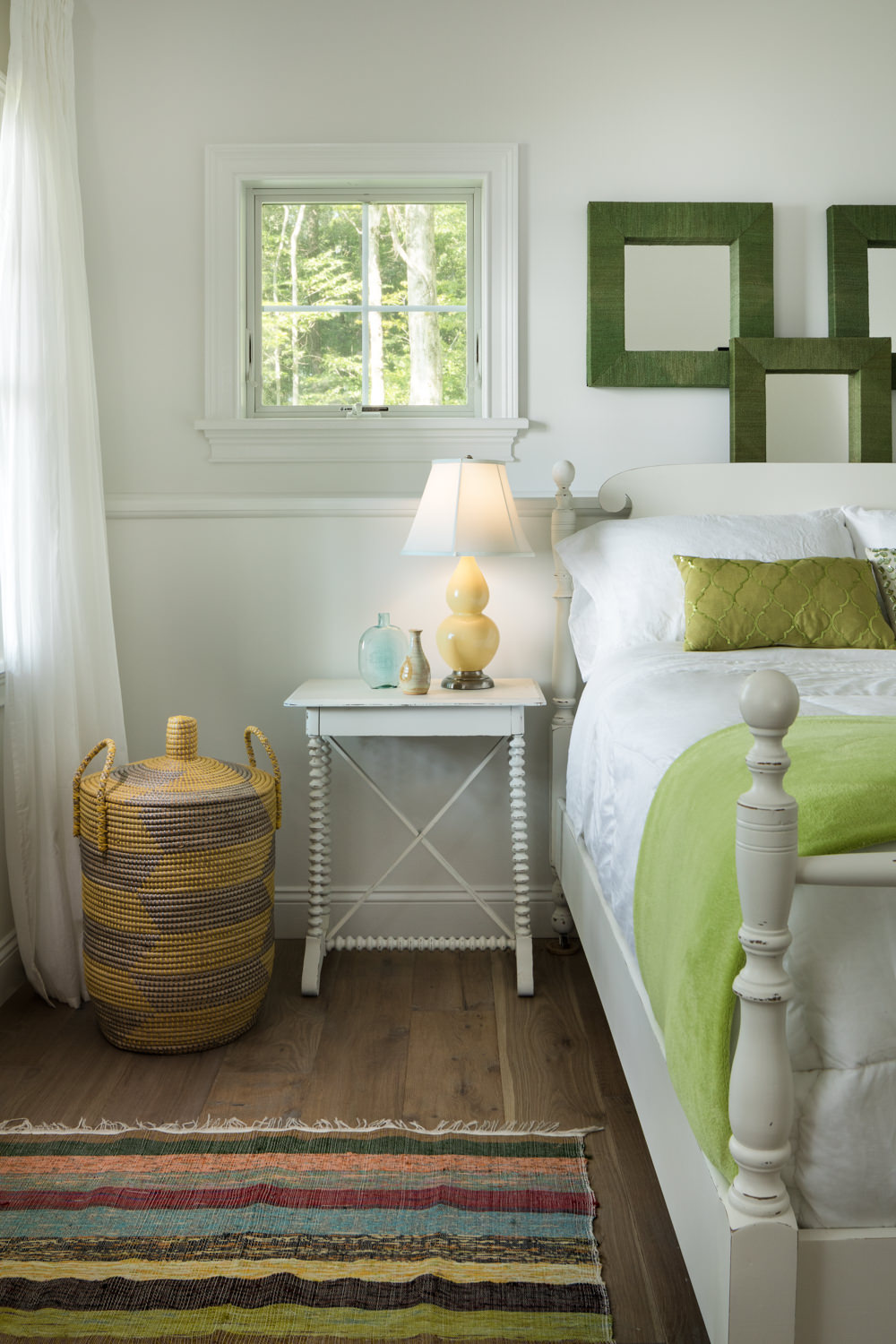 A photo of a rustic chic guest bedroom design with green accents, woven basket, hand tied rug and yellow lamp by photographer Stina Booth