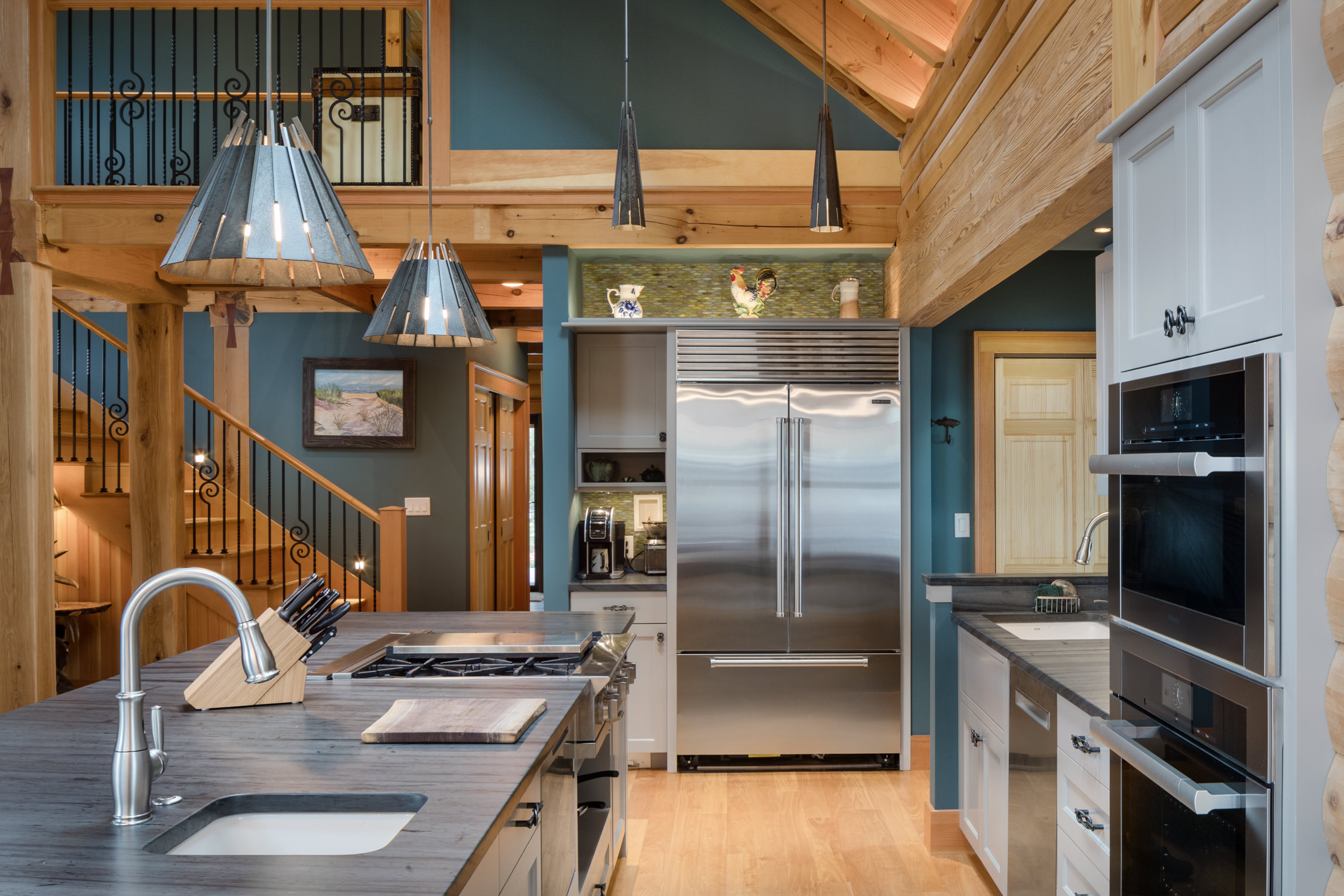Photo of an Adirondack style lake house renovation including an open kitchen and living concept, timber framing and wood paneling throughout designed by Wiemann Lamphere Architects and photographed by Vermont photographer Stina Booth of Studio SB.,