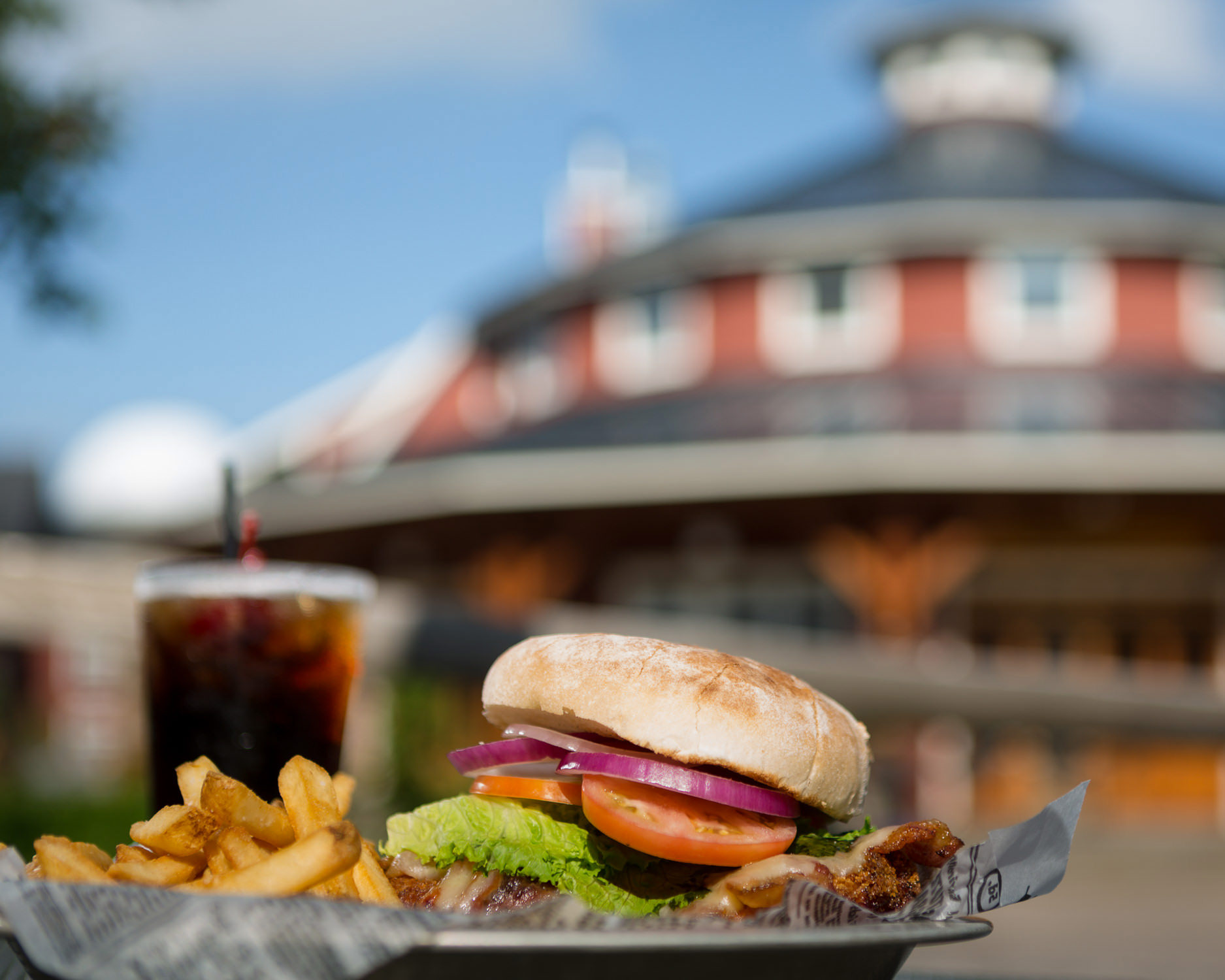 A burger and a basket of fries are seen on a patio table with the Timbers Restaurant in the background in a food photo by Stina Booth