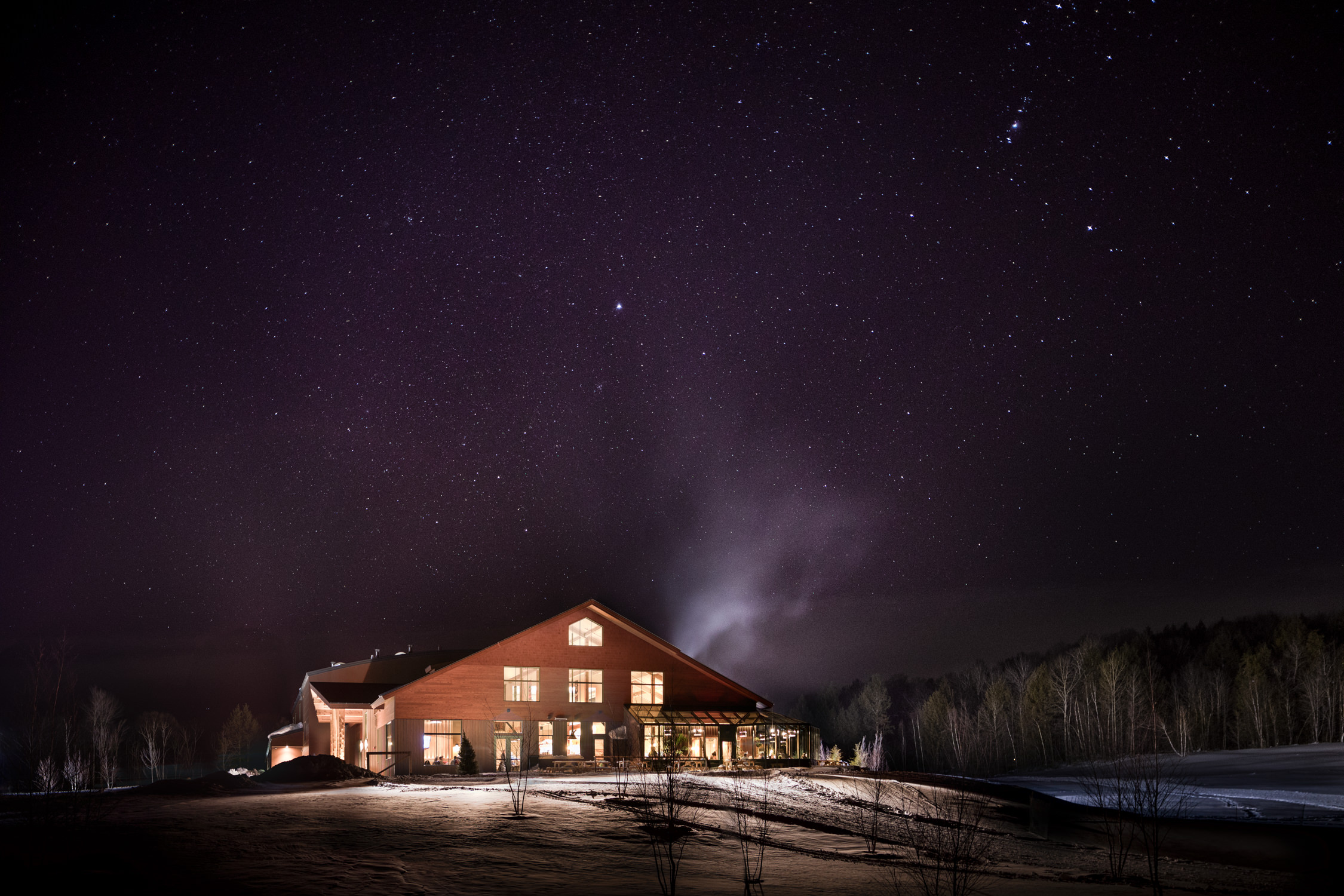Photo of the Trapp Bierhall in Stowe Vermont taken at night under a starry sky by Vermont architecture photographer Stina Booth