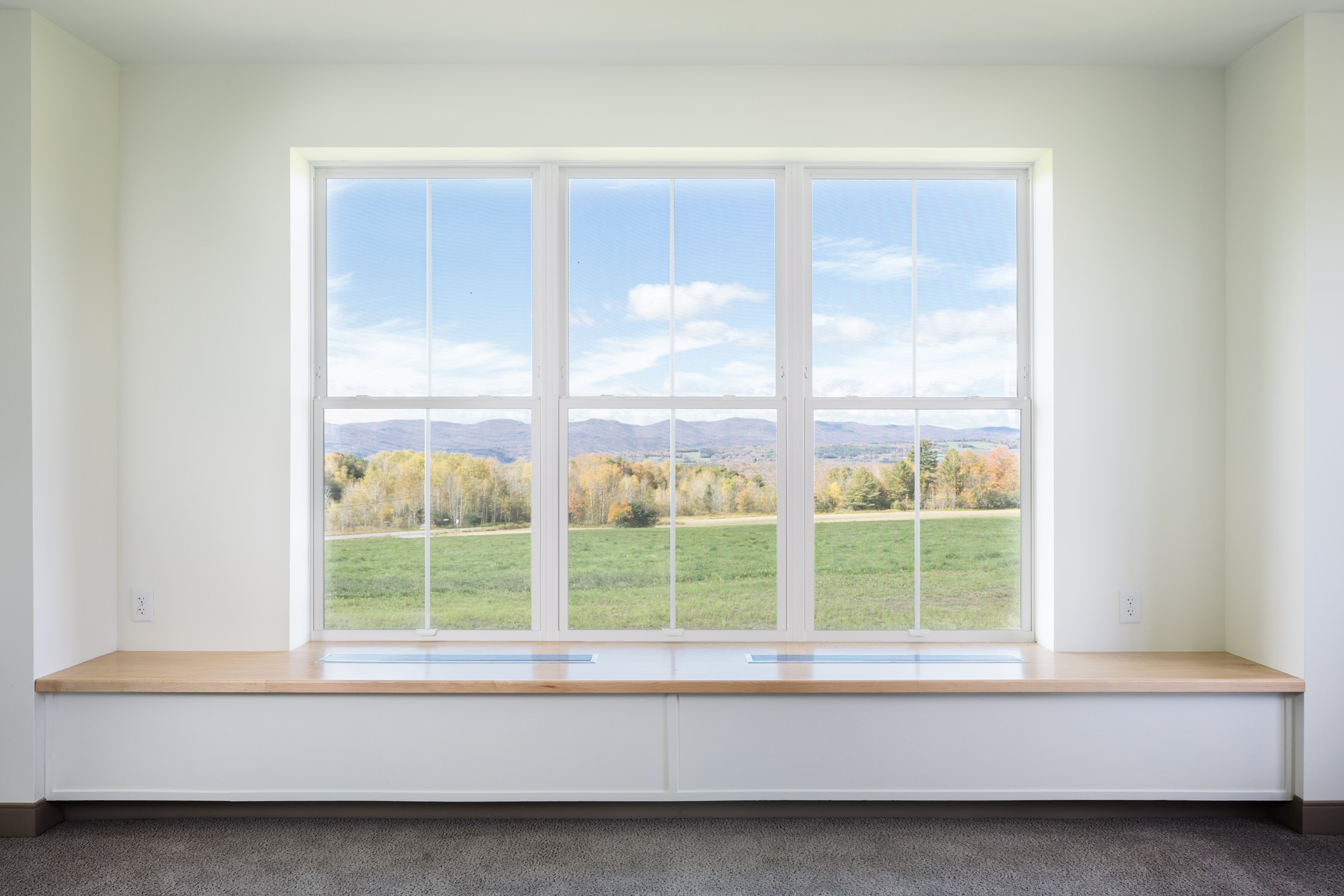 Photo of the eastward mountain view through the bench seat windows of a unit in the Strode Independent Living facility by Vermont architecture photographer Stina Booth
