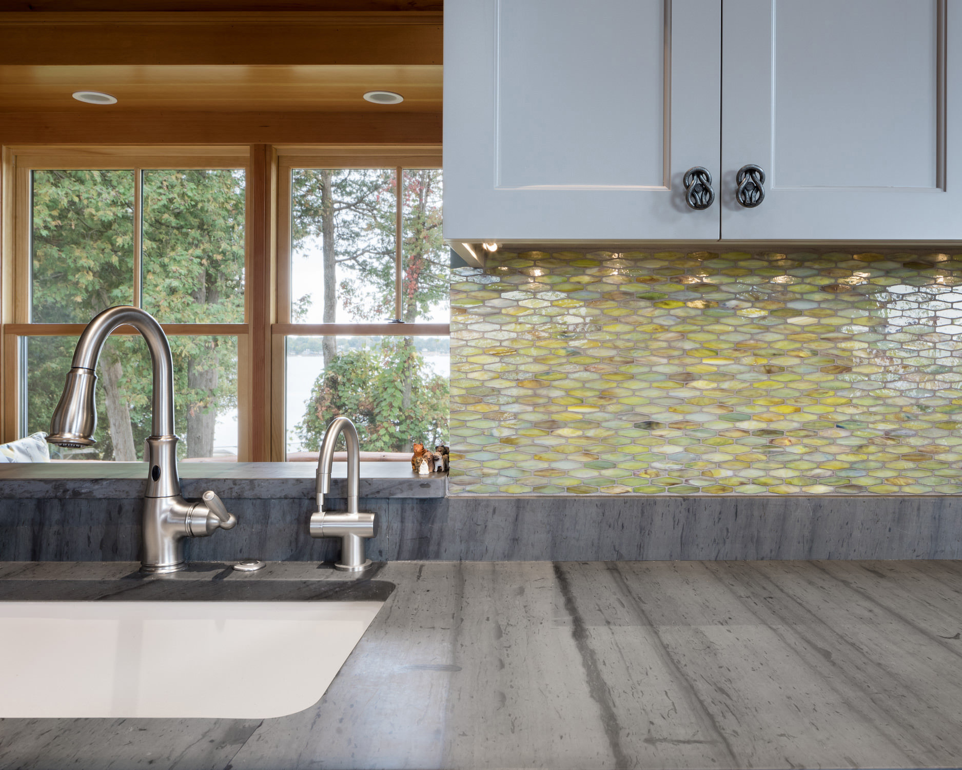 Interior architecture photo of a green glass tiled backsplash and soapstone counters in a kitchen renovation by Wiemann Lamphere Architects and photographed by Vermont photographer Stina Booth of Studio SB.,