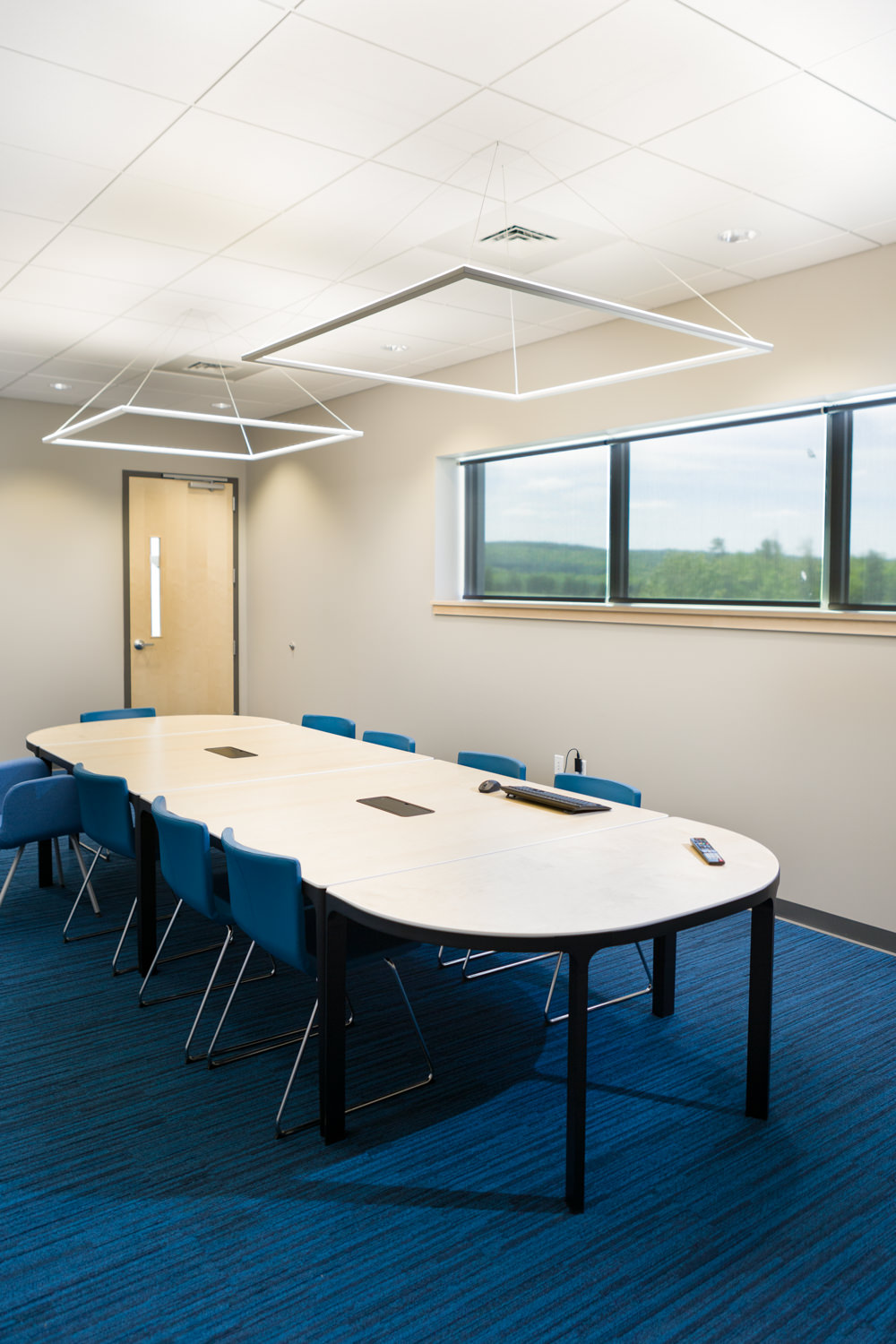 Blue conference room in Logic Supply building addition for Neagley & Chase Construction Company by Vermont architecture photographer Stina Booth of Studio SB.