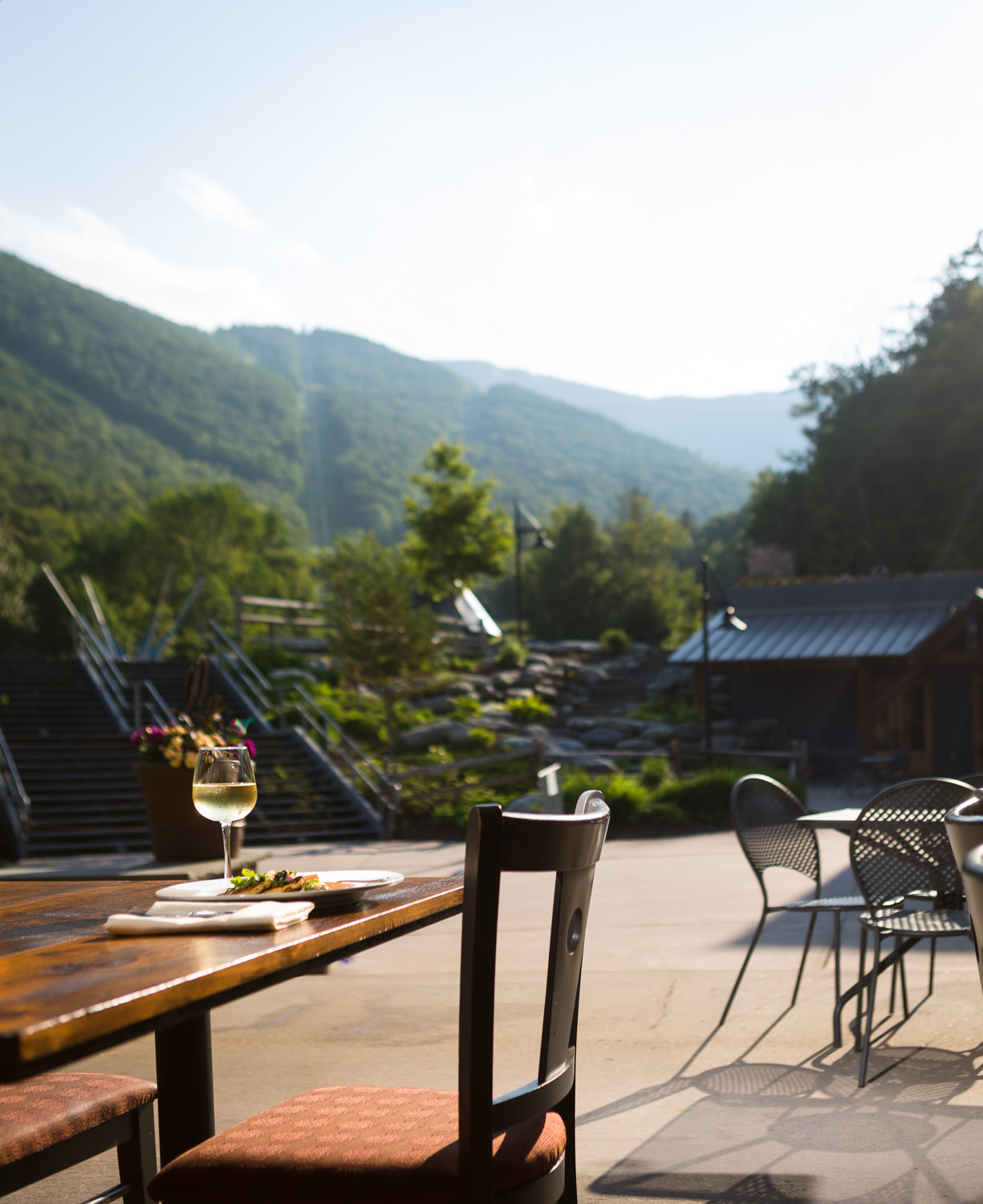 An entree from the Timbers Restaurant at the Sugarbush Resort in Vermont sits at an outdoor patio table with a view of the ski mountain in a food photo by photographer Stina Booth