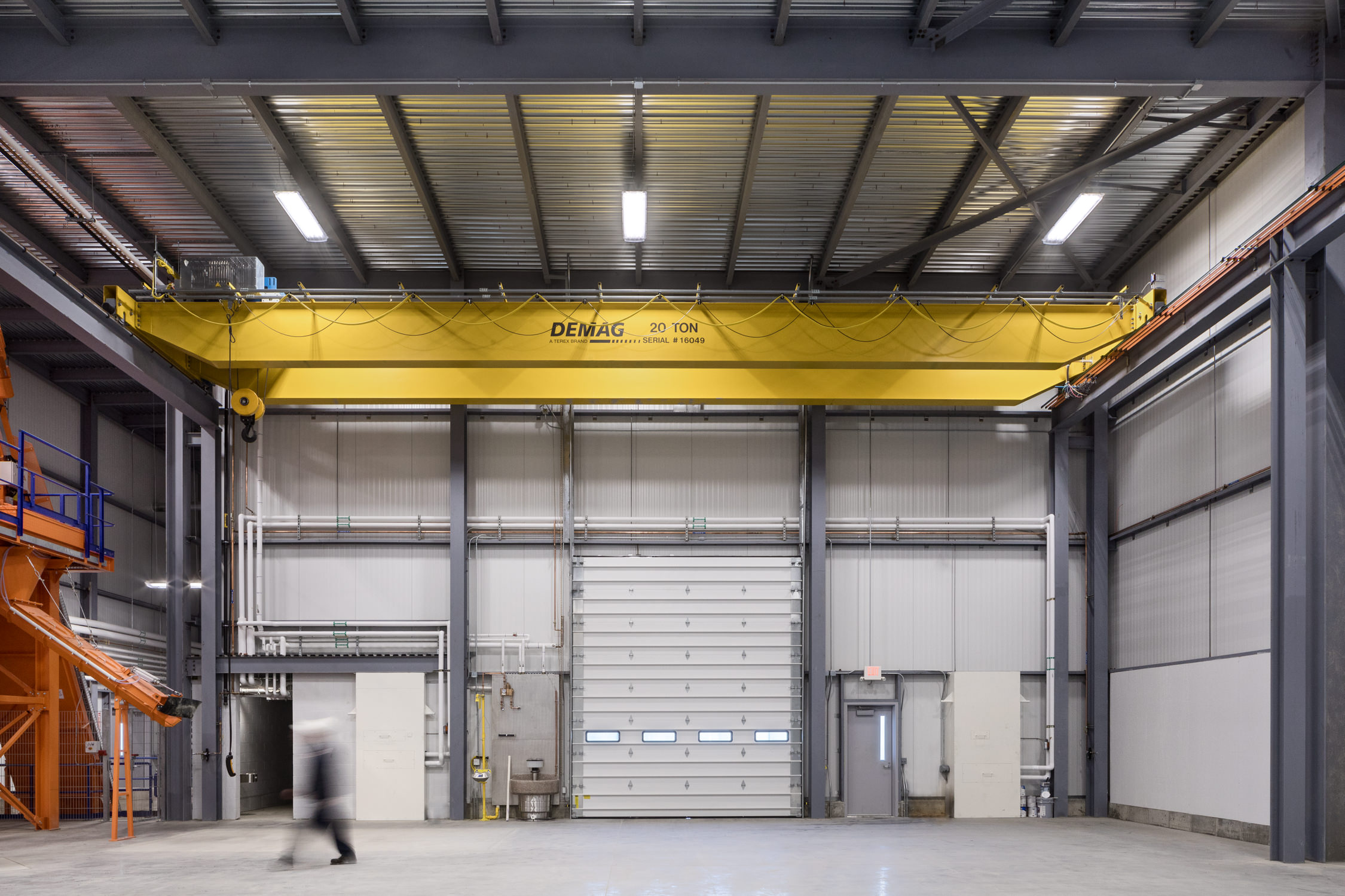 Photo of a blurred worker walking through a warehouse in the Camp Precast facility in Milton Vermont taken by commercial photographer Stina Booth