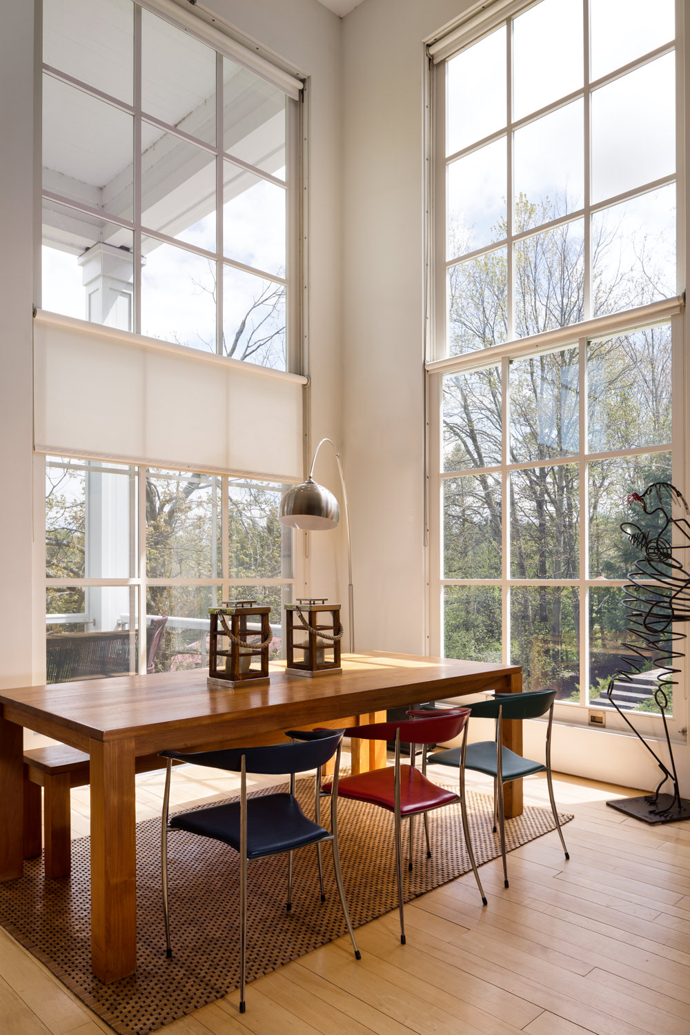 Vermont professional photographer Stina Booth captures the soaring floor to ceiling pane glass windows in a contemporary dining room