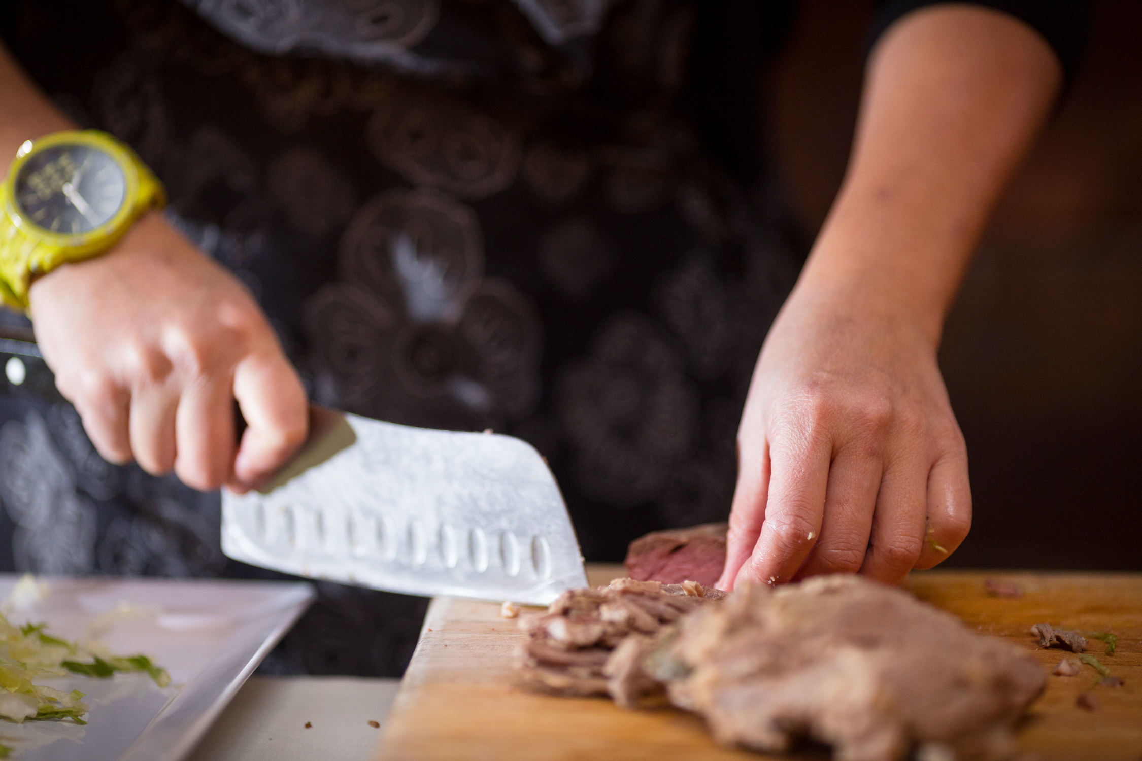 The deft hands of a chef wield a butcher knife to slice steaks in a food photograph by Stina Booth