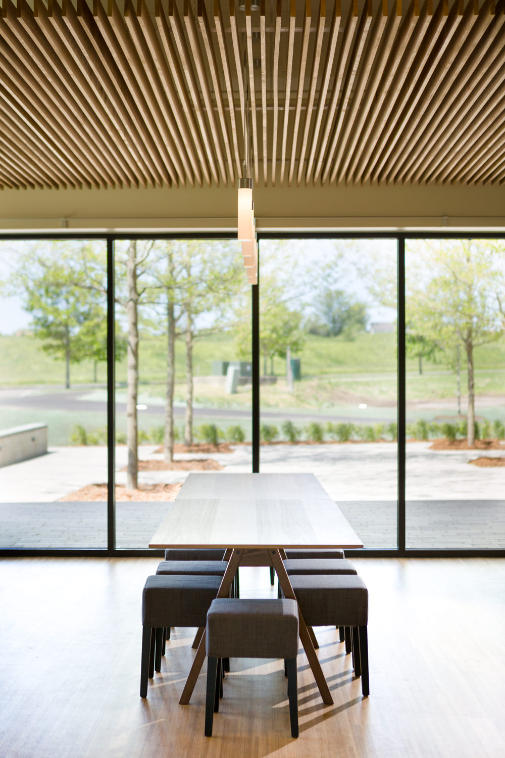 Picture of modern cafeteria tables with pendant lights and wood slat ceiling in the Logic Supply addition by Vermont architecture photographer Stina Booth of Studio SB.