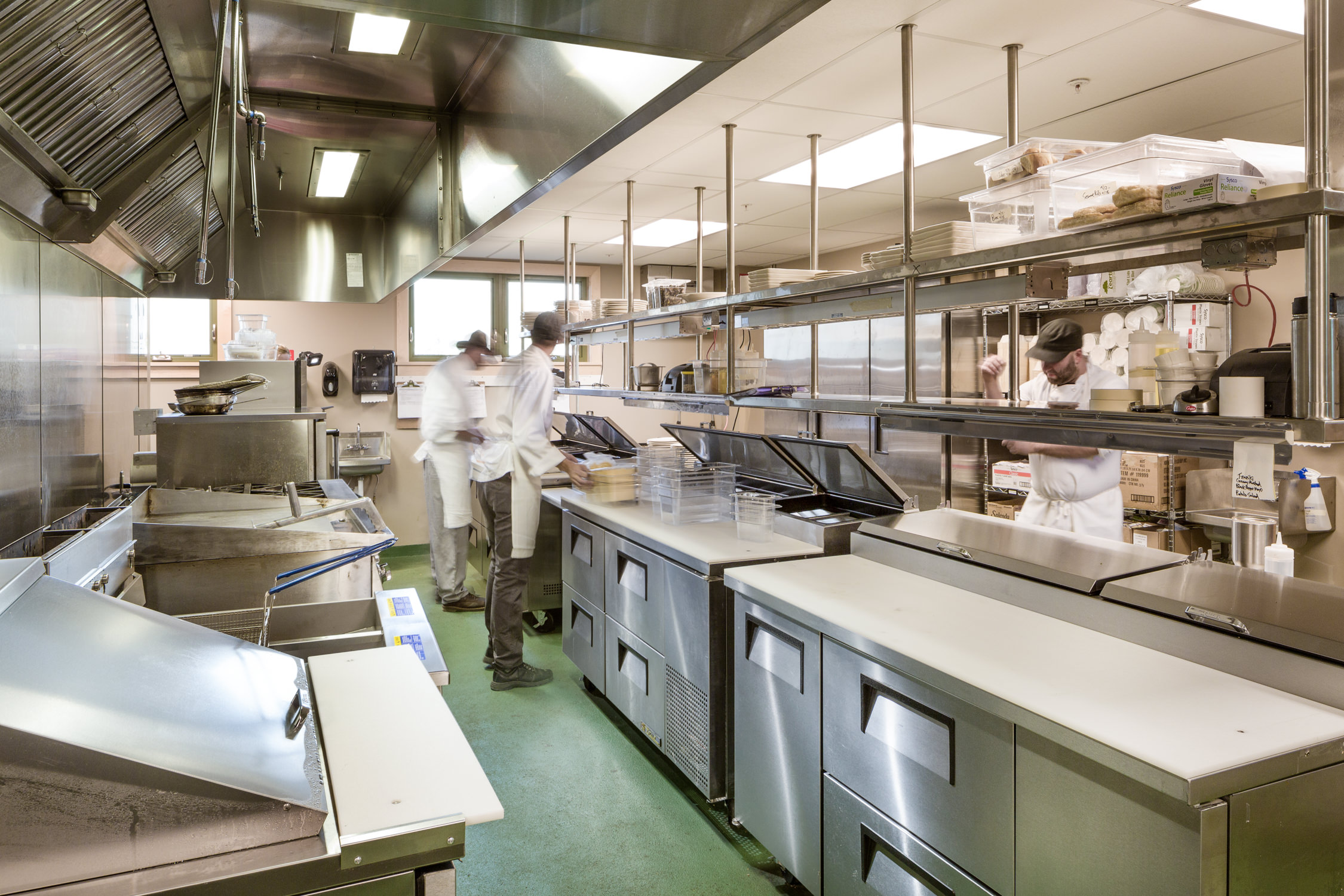 A photo of sous chefs busily prepping for dinner in the commercial kitchen at the von Trapp Brewery Bierhall by architecture photographer Stina Booth