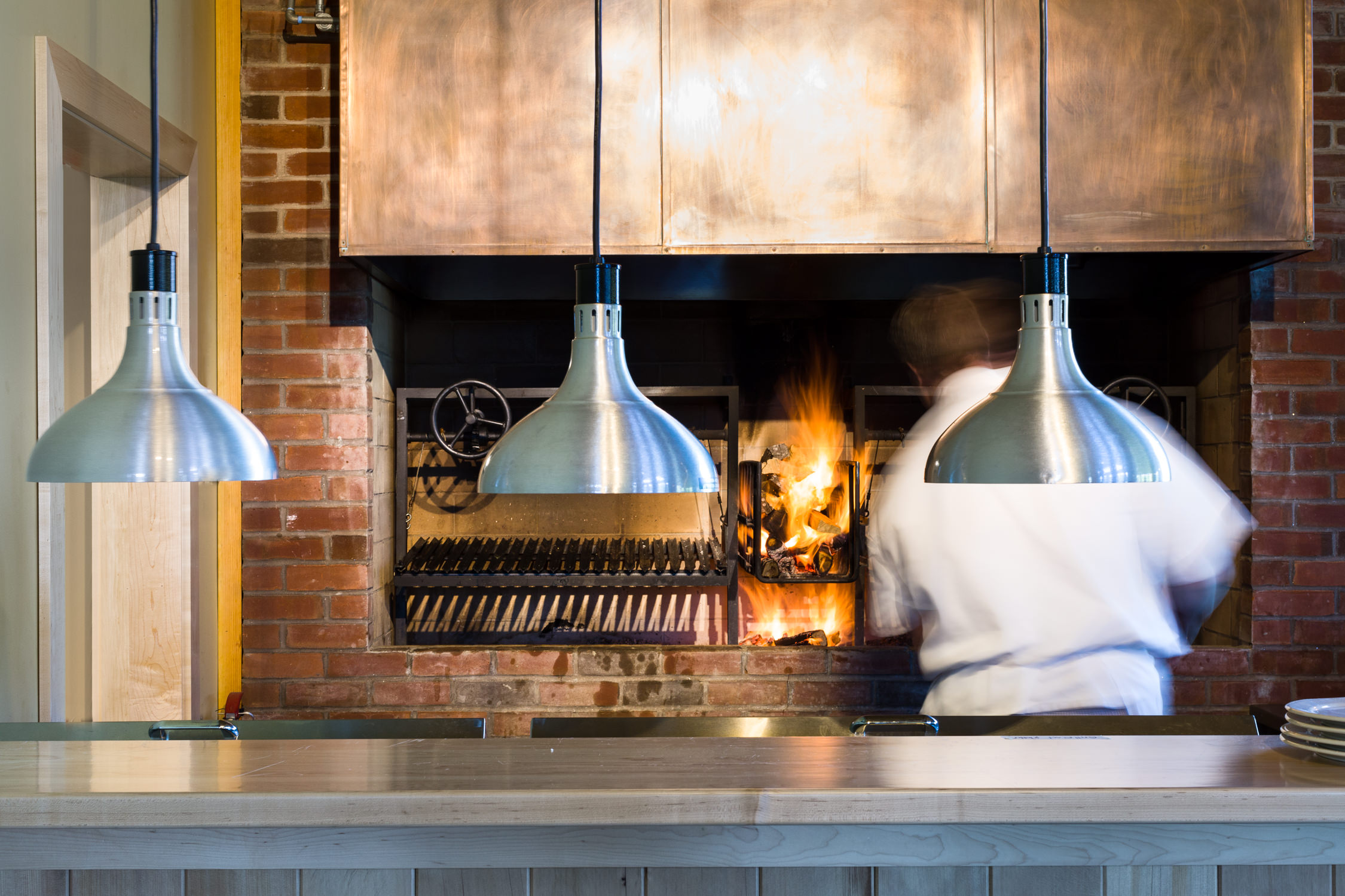 A chef preps the fire in a wood fired oven at the von Trapp Brewery Bierhall in Stowe Vermont in a photo by commercial photographer Stina Booth