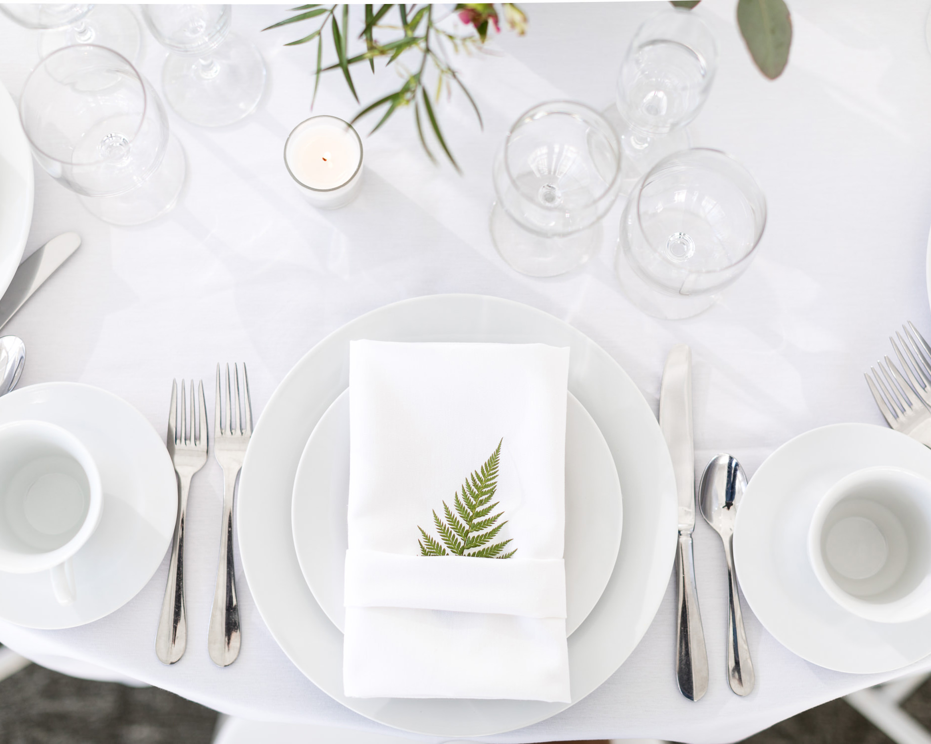 A green fern is tucked inside a white napkin in a styled wedding table setting at the Essex Resort by photographer Stina Booth