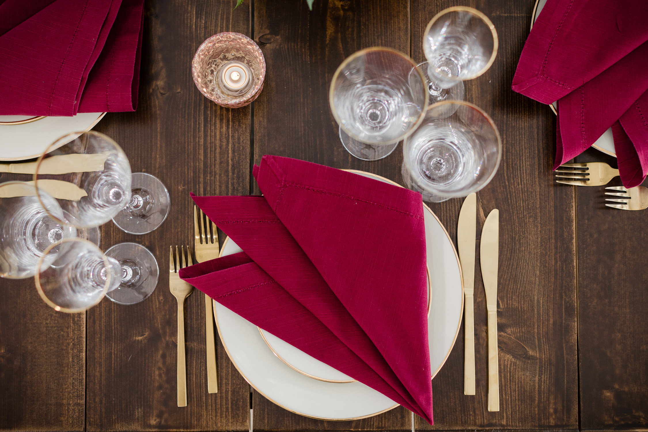 Cranberry linens and gold flatware are set on a farmhouse wood table from the Vermont Tent Company in a styled wedding table setting at the Essex Resort by photographer Stina Booth