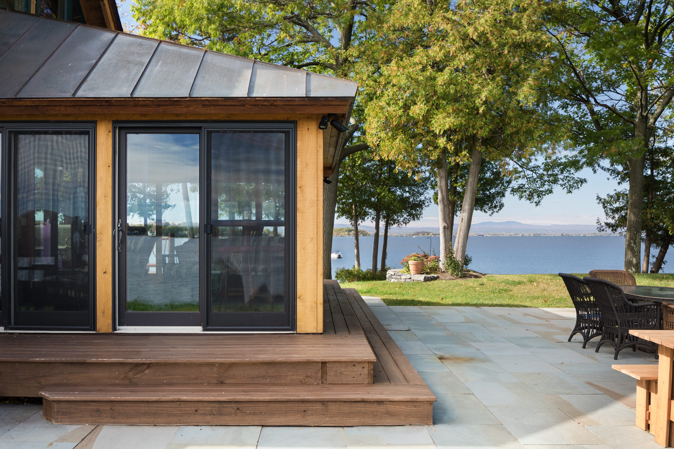 Exterior photo of the sunroom and surrounding lake views in an Adirondack style lake house renovation by Wiemann Lamphere Architects and photographed by Vermont photographer Stina Booth of Studio SB.,
