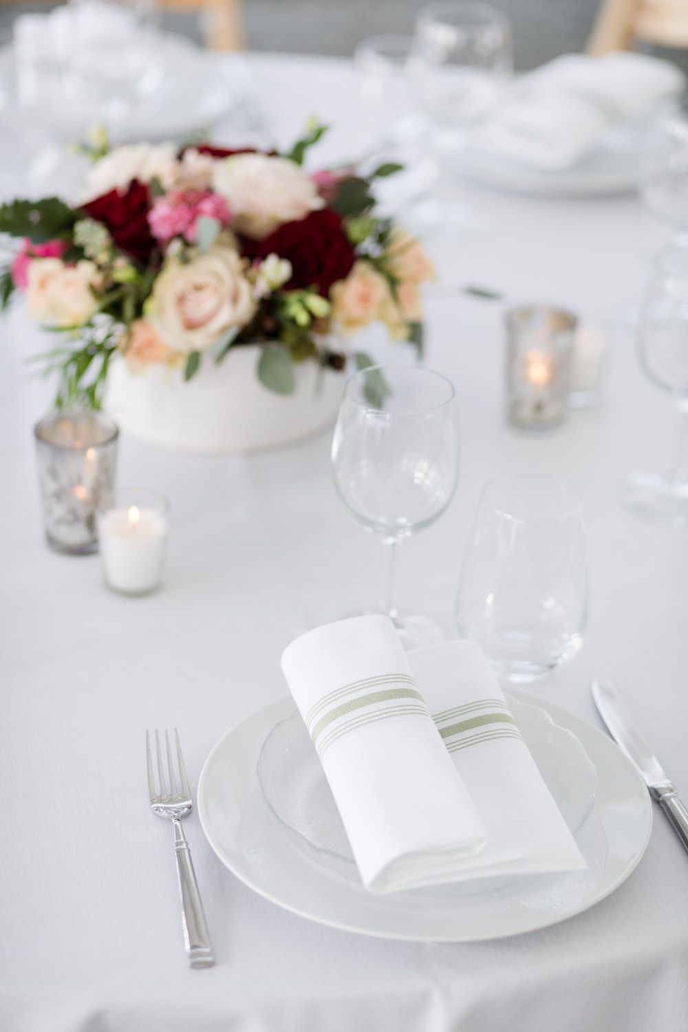 A gem toned centerpiece is paired with crisp white linens in a styled wedding table setting at the Essex Resort by photographer Stina Booth