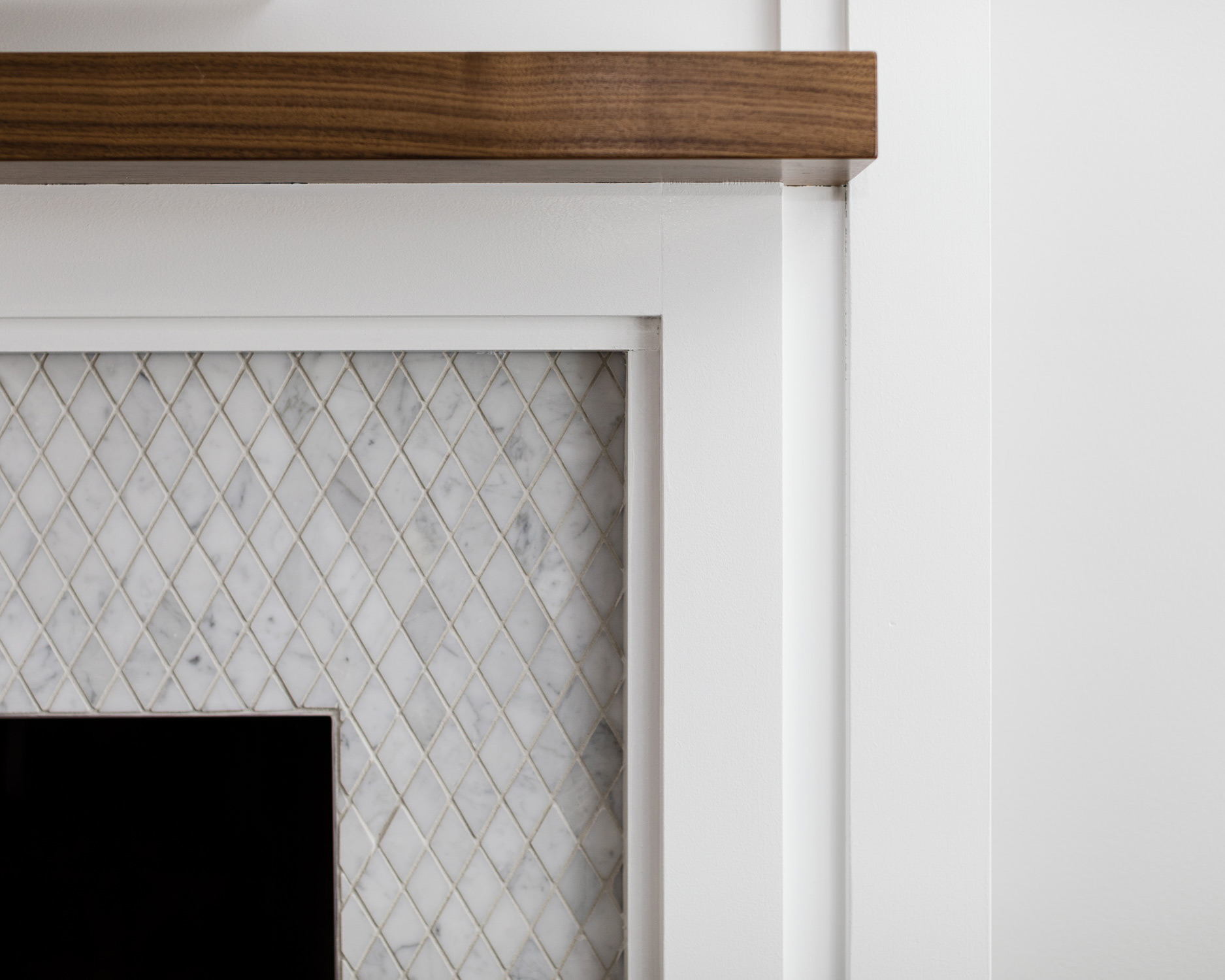 Photo of marble tiled fireplace by professional photographer Stina Booth of open concept remodel in Burlington Vermont by Roots Design Studio