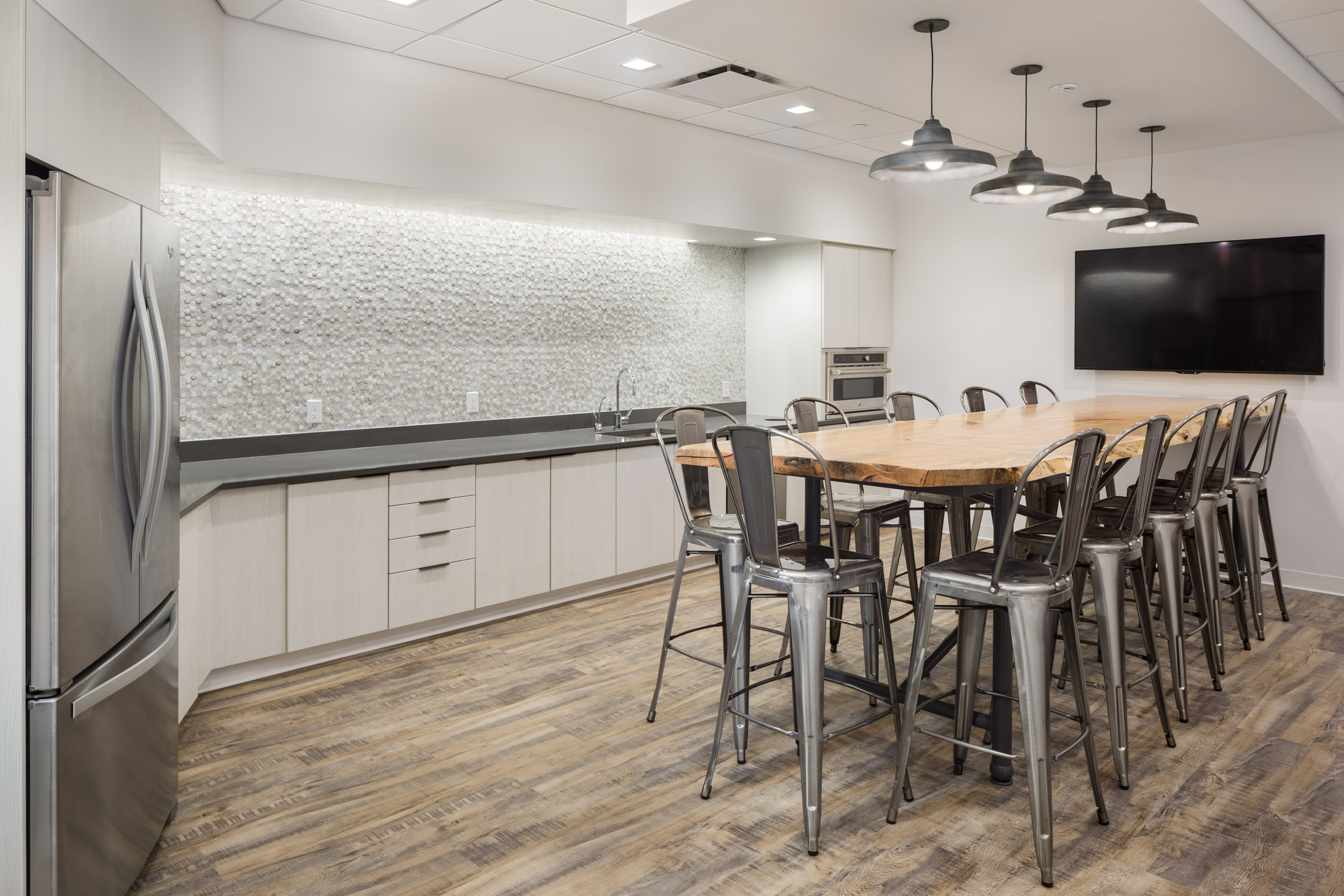 An overall photo of the modern hex wall tile, undermount stainless steel sink, industrial stools and raw edge wood table in the employee lunch room at KPMG in Vermont taken by professional photographer Stina Booth