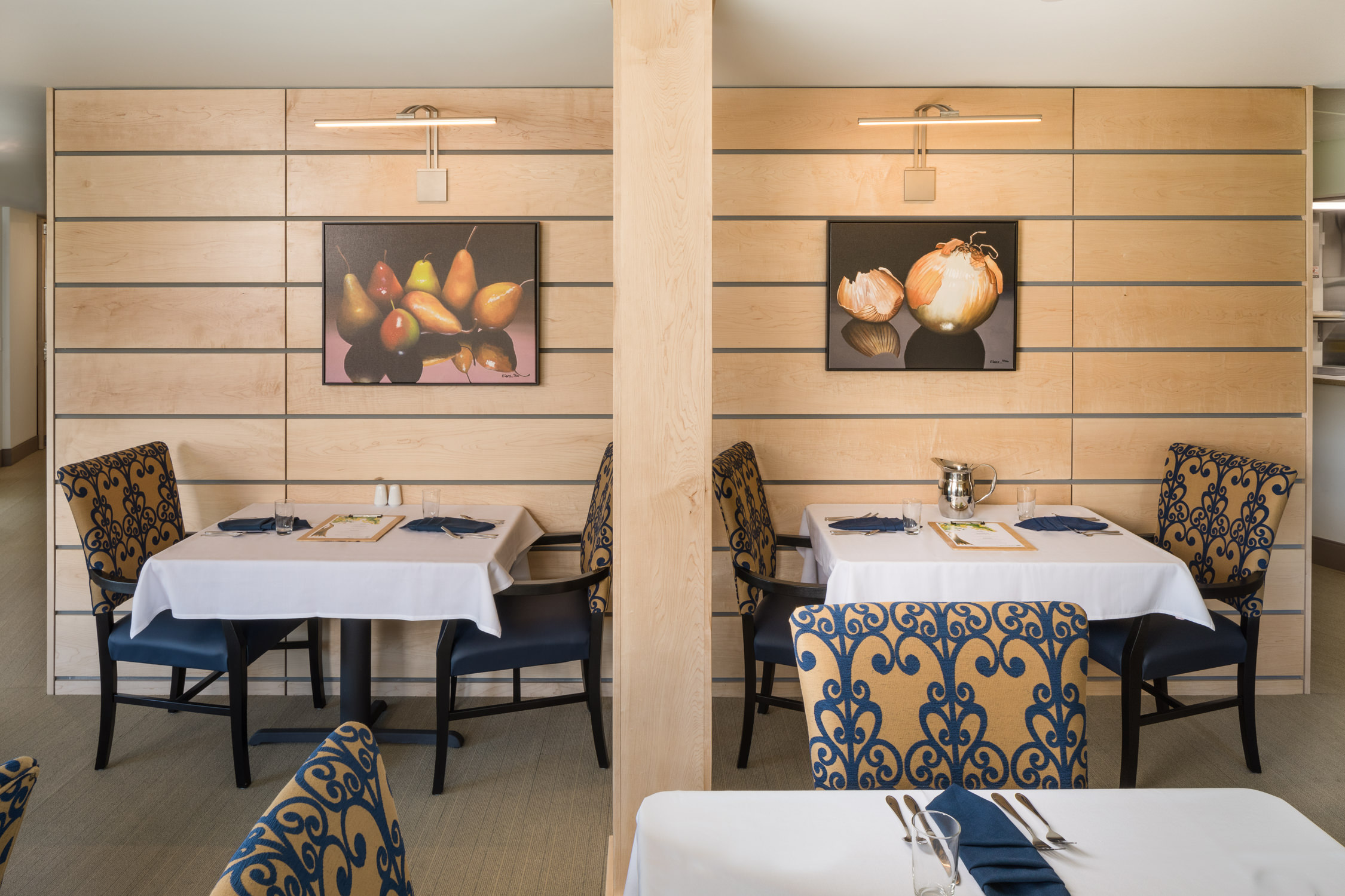 A photo by Stina Booth of tables set against the wood slatted art wall in the main dining room of the Strode Independent Living facility in Randolph Vermont