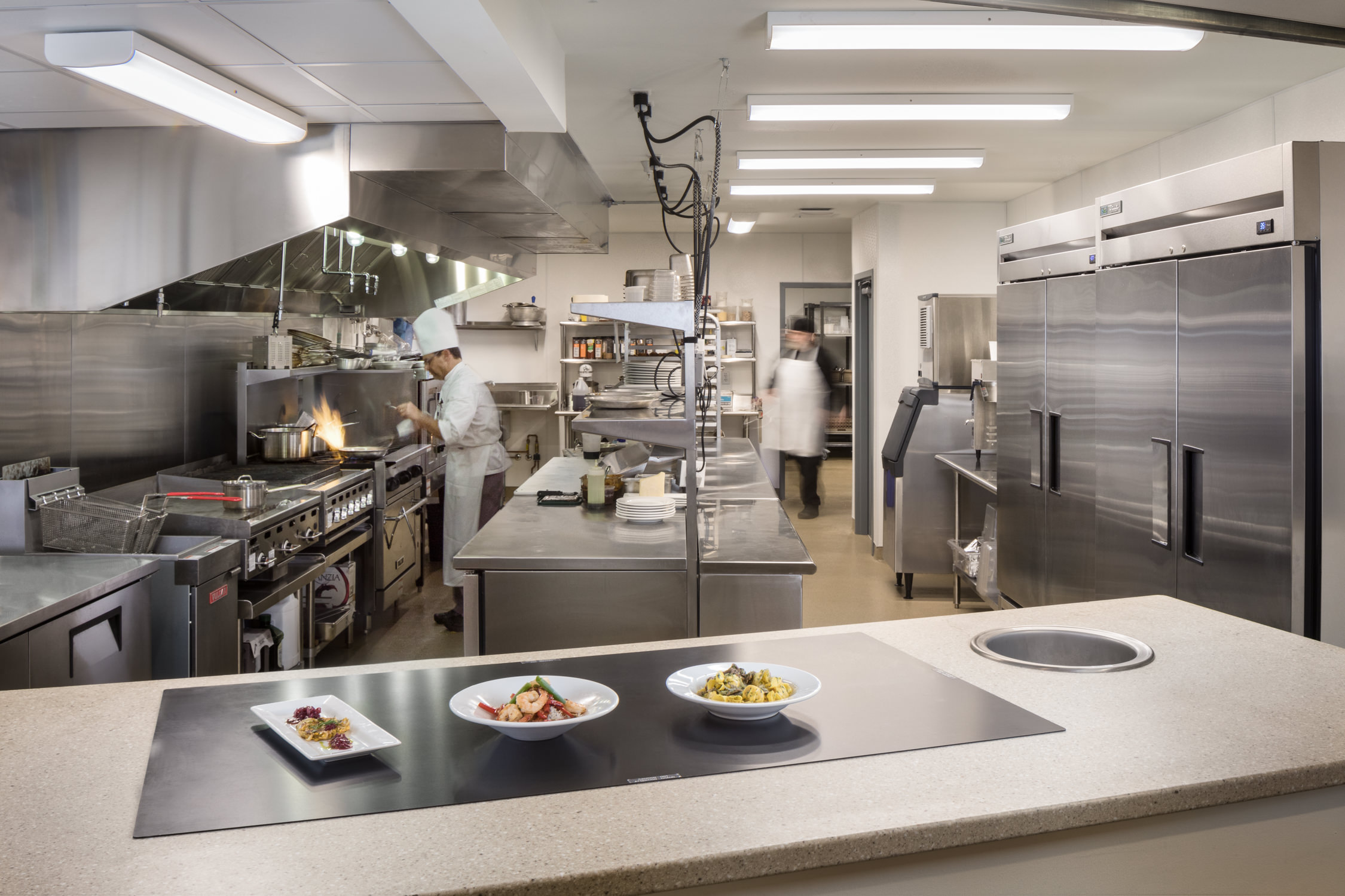 A photo by Stina Booth of chefs working the commercial kitchen of the Strode Independent Living Facility in Randolph Vermont