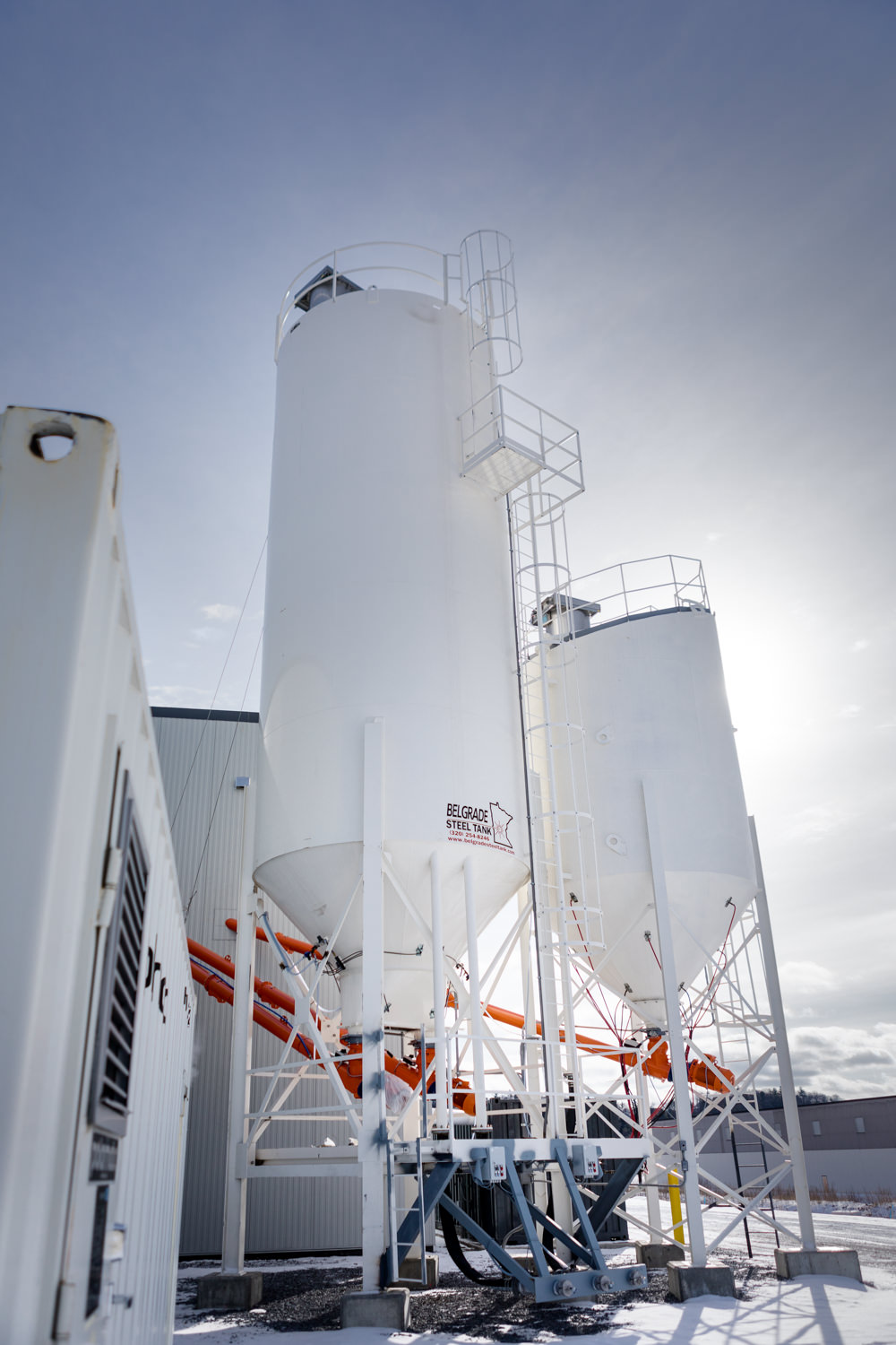 A photo of material silos under a blue sky at Camp Precast in Milton Vermont by professional photographer Stina Booth