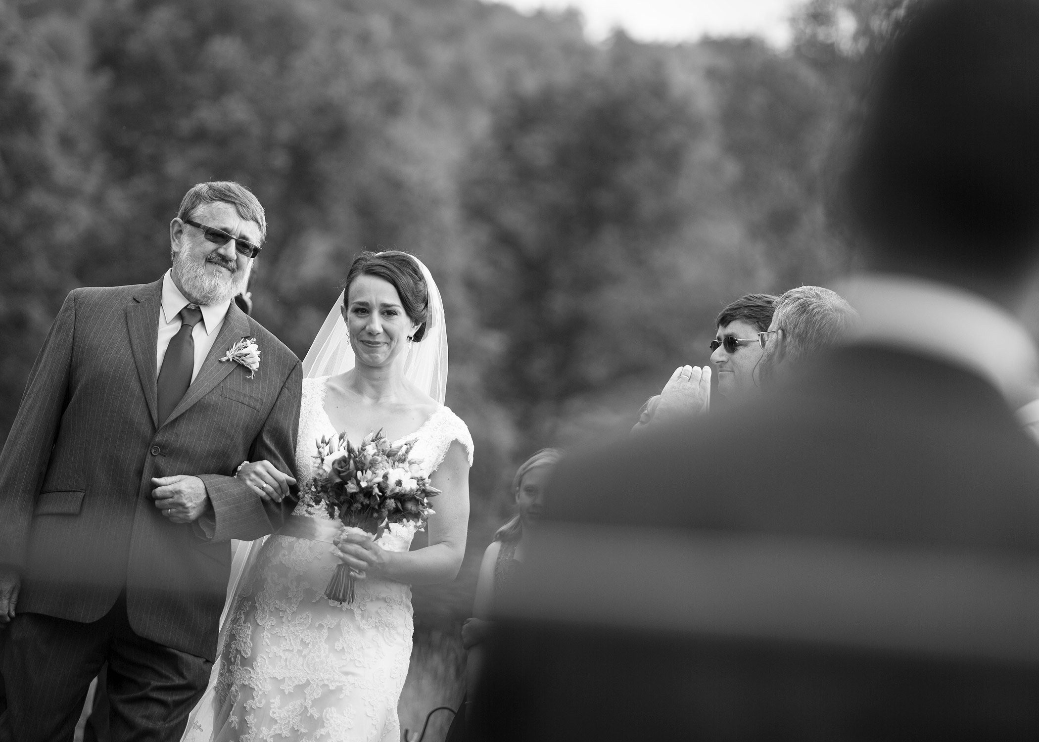 A bride is seen walking down the aisle with her father over the shoulder of the groom during a wedding at Bliss Ridge by Vermont wedding photographer Stina Booth