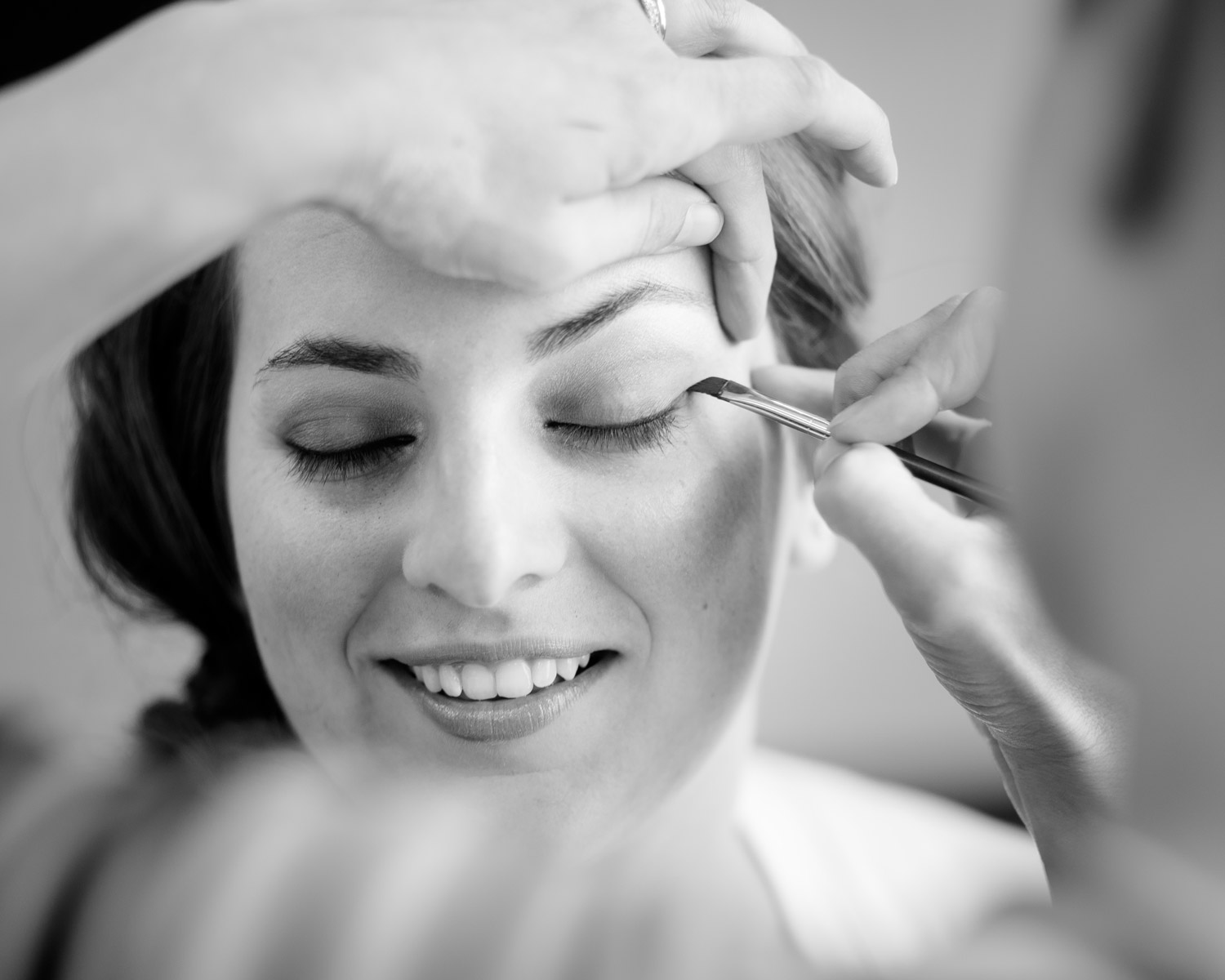 A bride getting eye making applied before her wedding by Vermont photographer Stina Booth